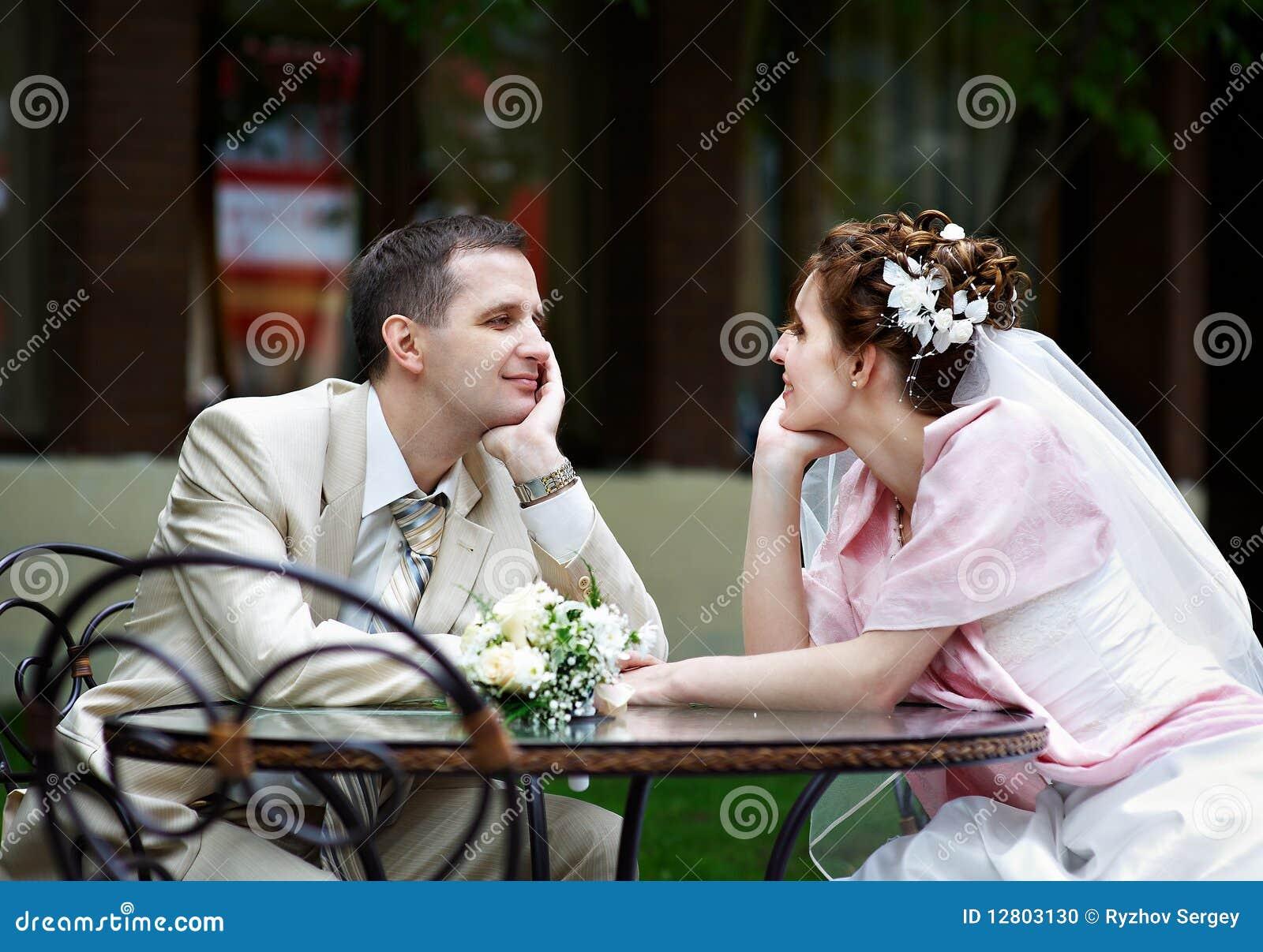 A noiva e o noivo felizes sentam-se na tabela no café