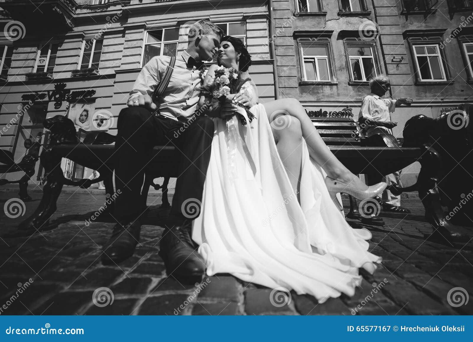 A noiva e o noivo sentam-se no banco