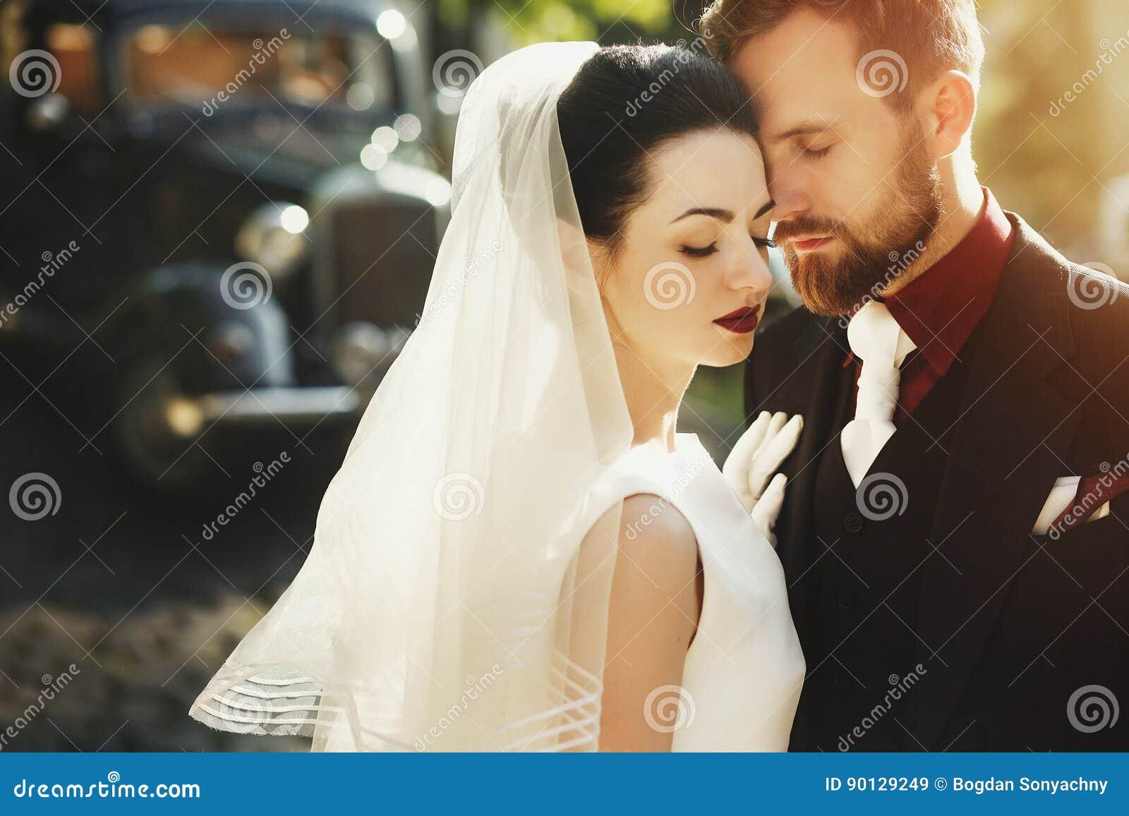 A noiva elegante lindo e o noivo à moda que abraçam, domam o toque