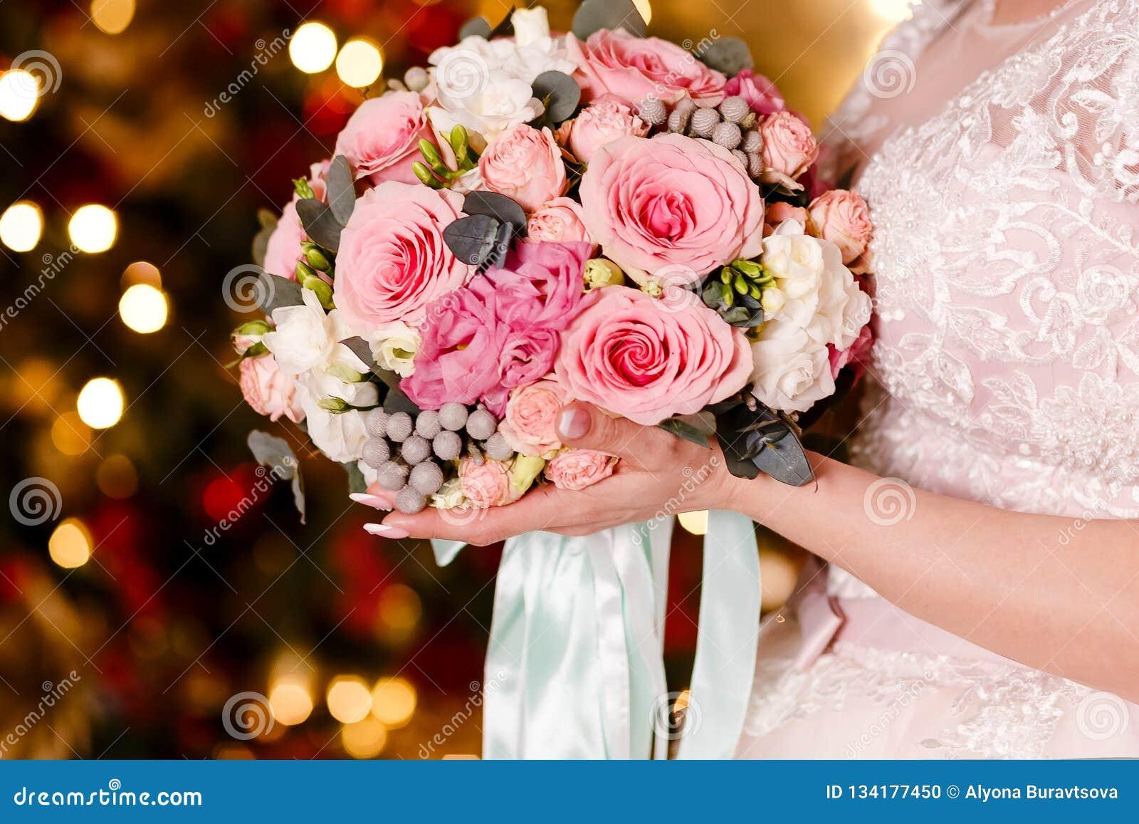 A noiva em um véu guarda um ramalhete bonito de rosas delicadas As luzes no fundo Tratamento de mãos francês em pregos ` S das mu