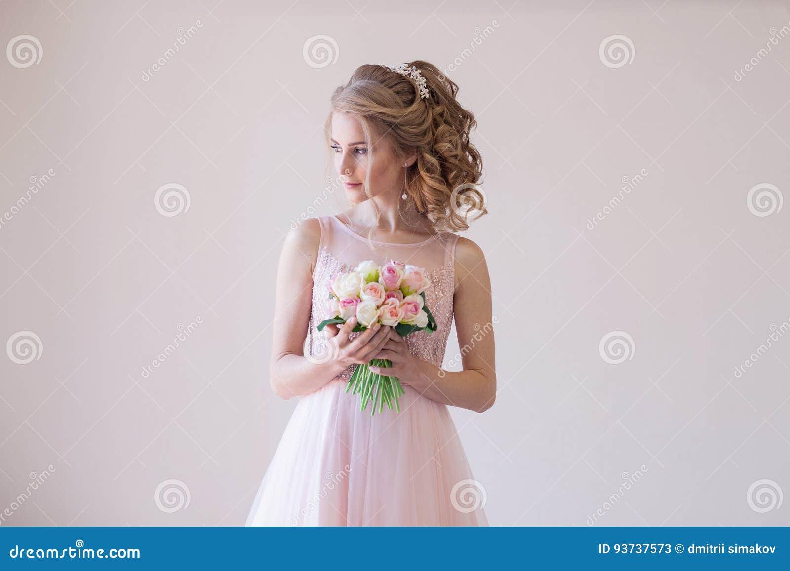 Noiva em um vestido de casamento e em um ramalhete cor-de-rosa das flores