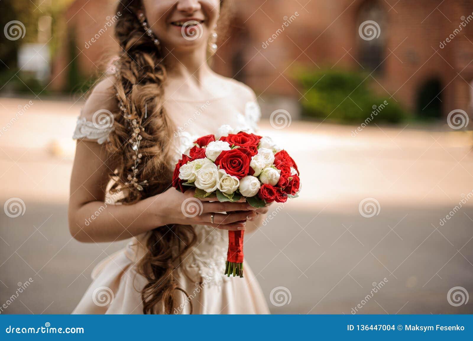 Noiva feliz de sorriso em um vestido de casamento com um penteado da trança que guarda um ramalhete das rosas