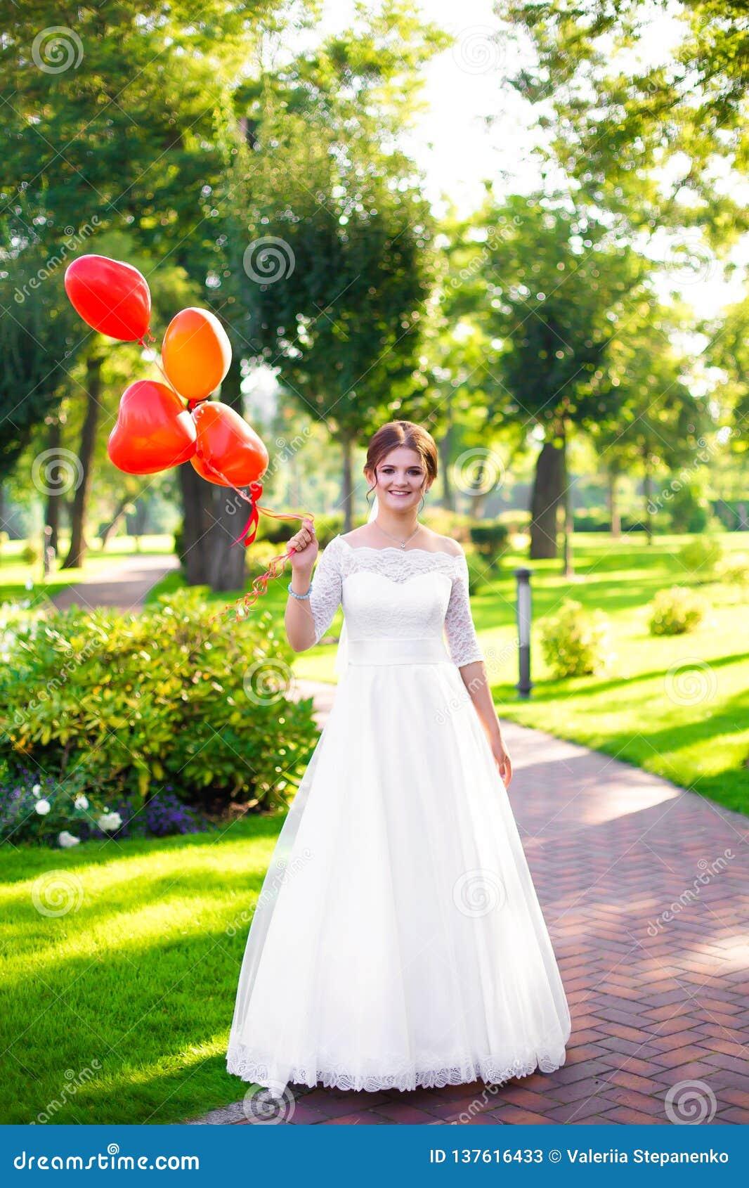 A noiva guarda balões vermelhos em sua mão