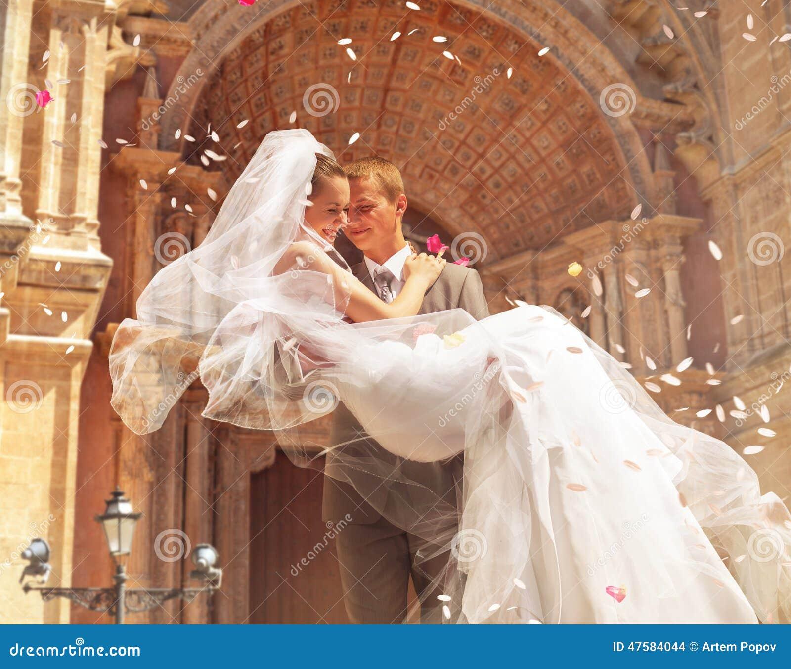 Noiva levando do noivo perto da igreja
