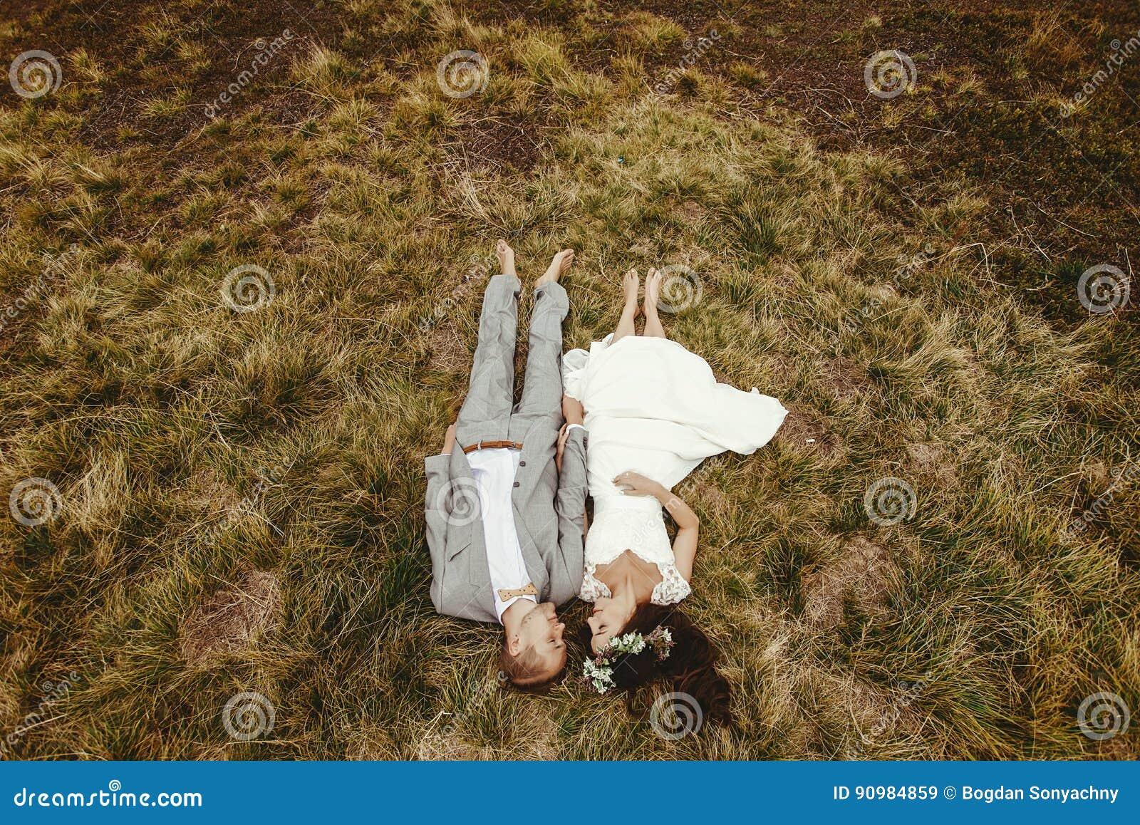 Noiva lindo e noivo à moda que encontram-se na parte superior, cou do casamento do boho