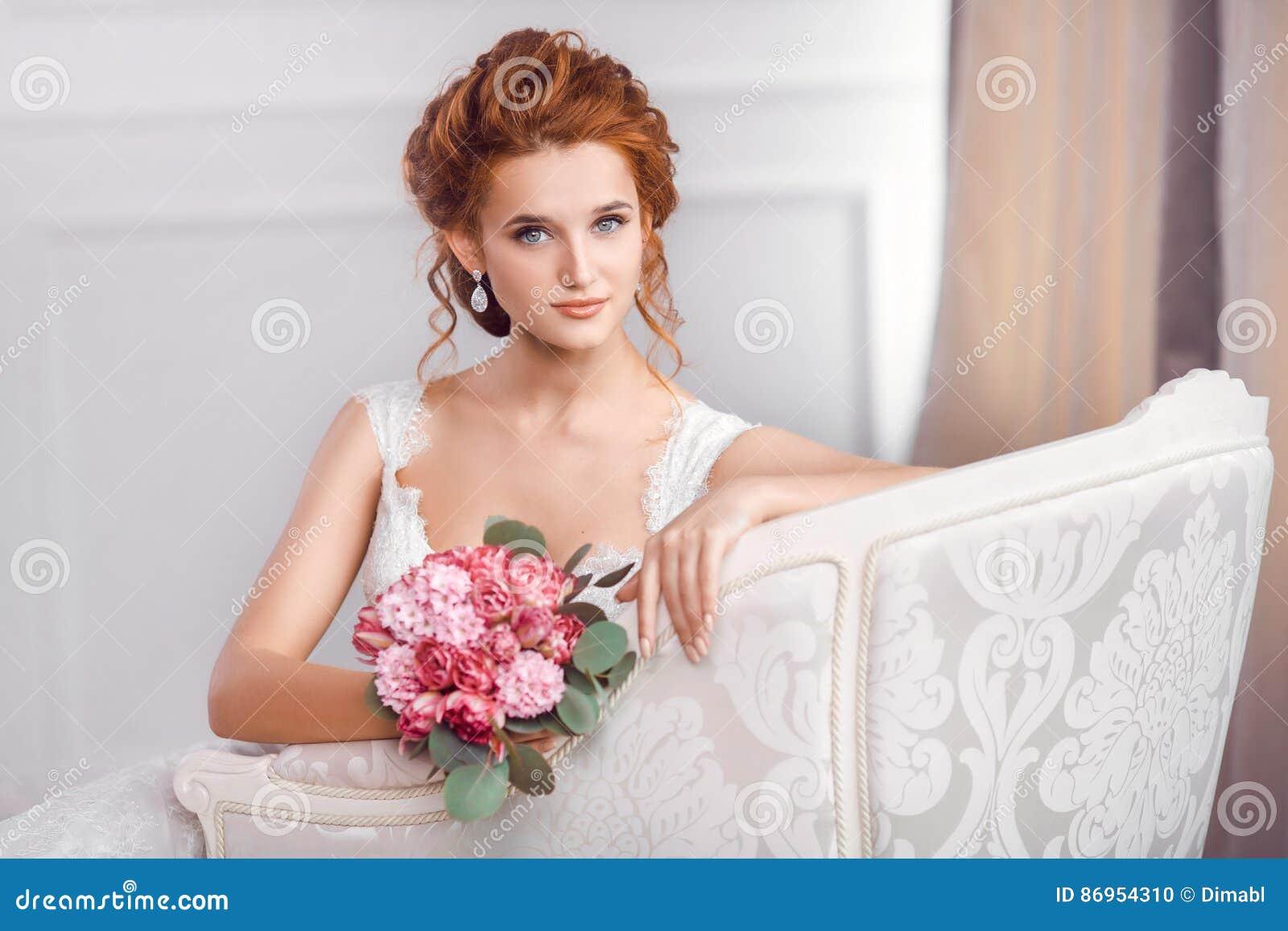 Noiva no descanso de assento do vestido bonito no sofá dentro