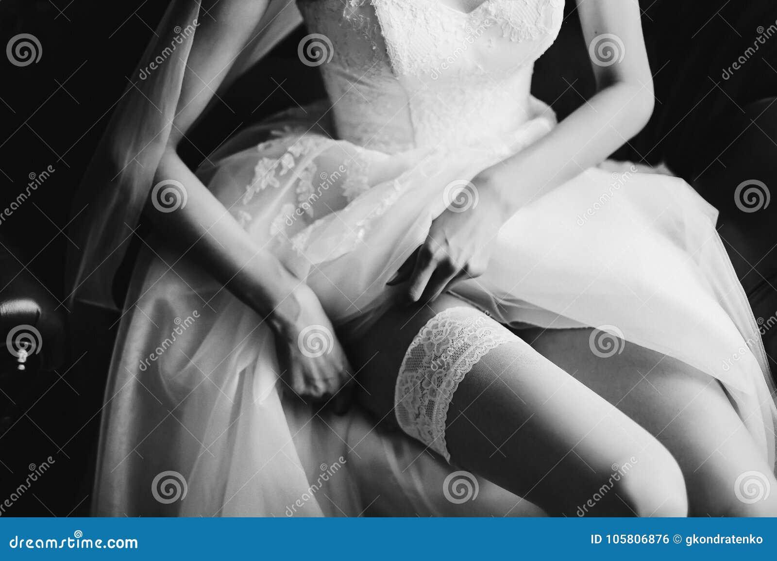 Noiva no vestido e em meias clássicos elegantes de casamento Manhã da noiva