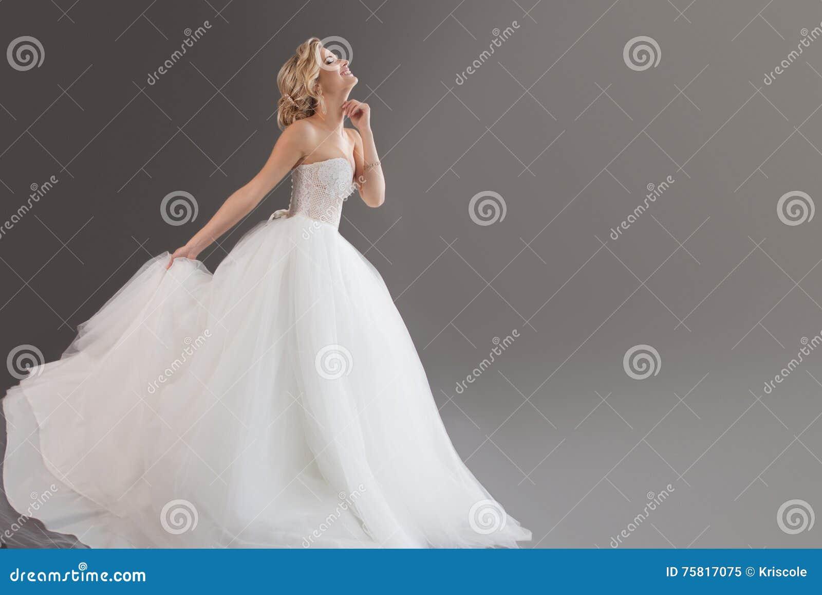 Noiva nova encantador no vestido de casamento luxuoso Menina bonita no branco Emoções da felicidade, do riso e do sorriso, cinzen