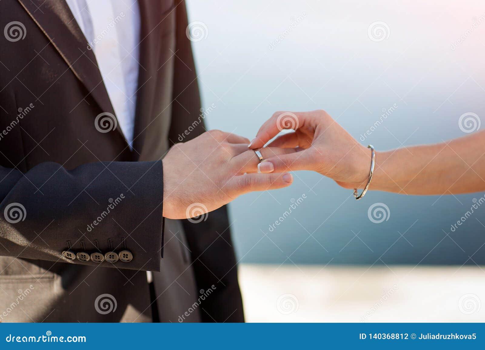 A noiva põe um anel sobre a mão do noivo
