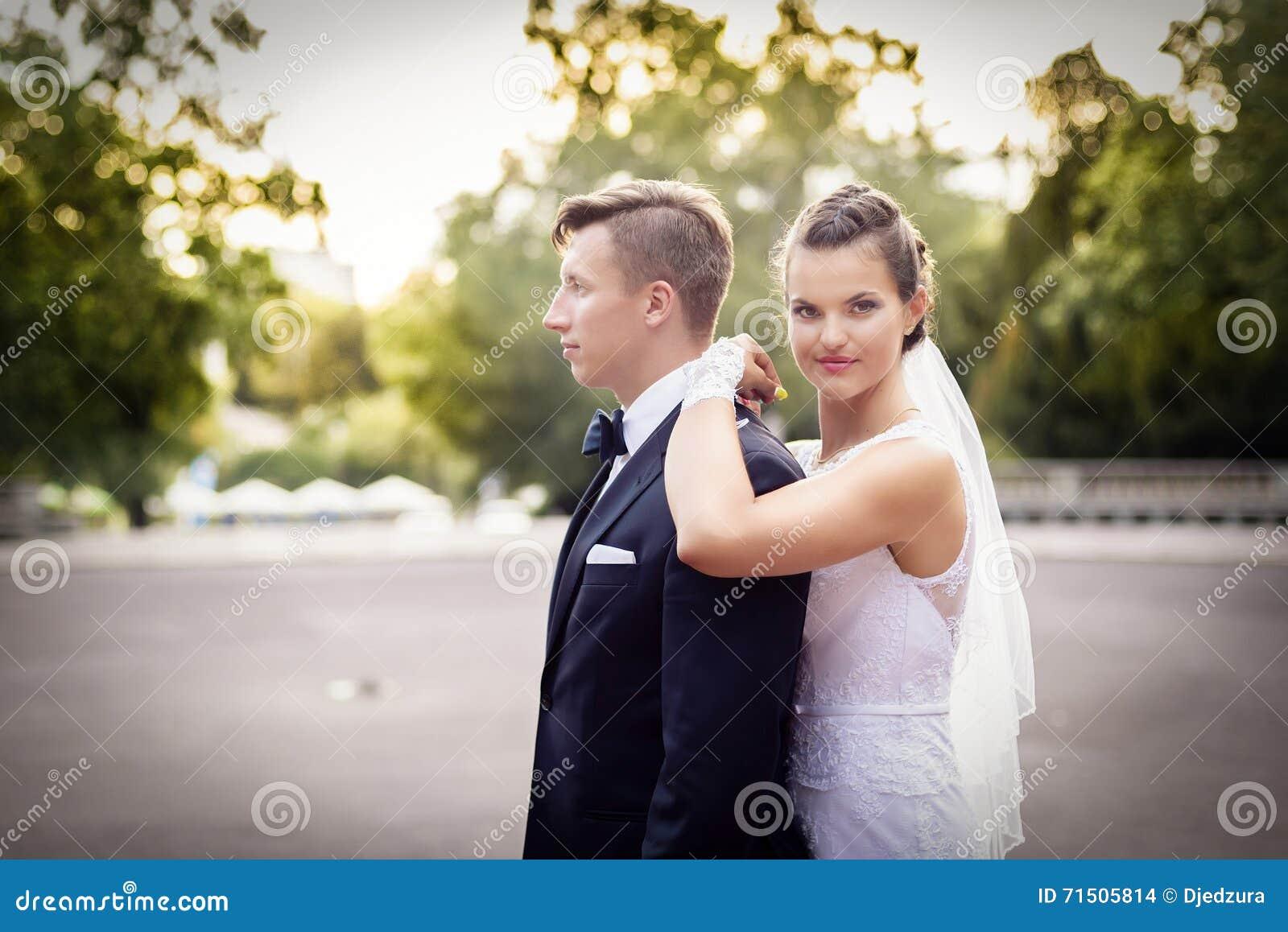 Noiva que está atrás do noivo e que olha a câmera