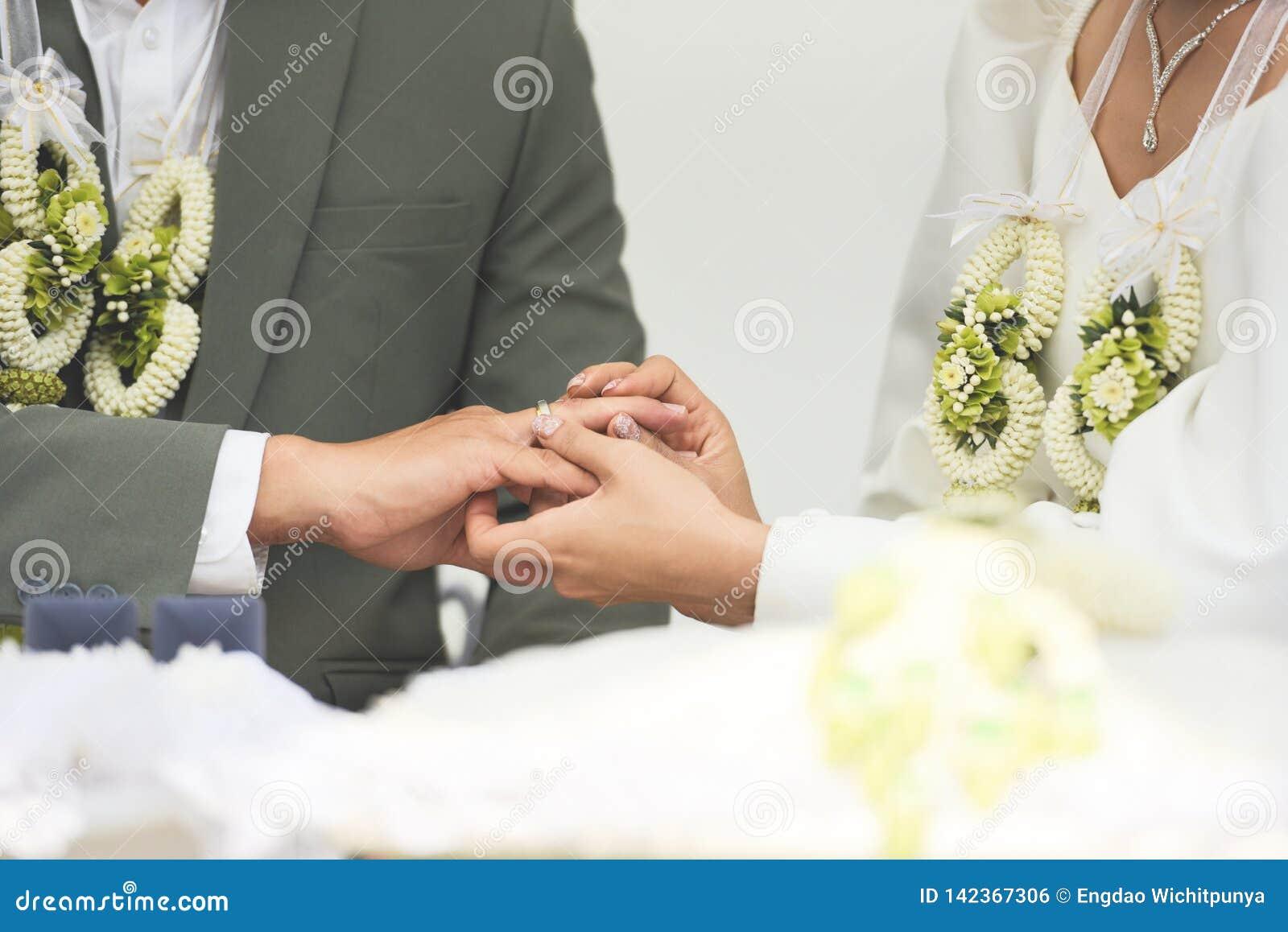 A noiva veste uma aliança de casamento no noivo no dedo de anel do assistente em seu dia do casamento