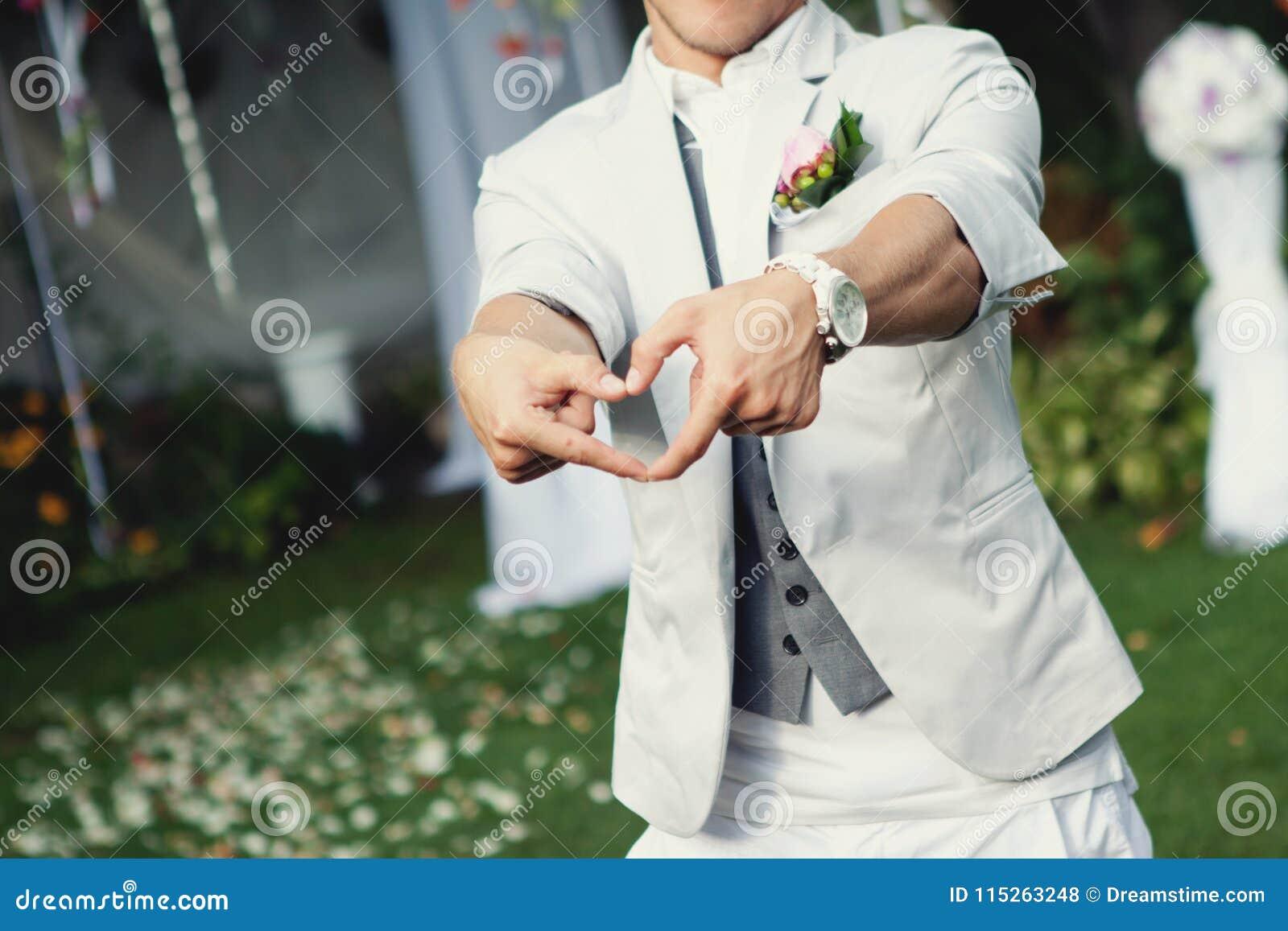 Noivo à moda feliz que faz uma forma do coração com mãos Noivo em um terno brilhante com um pulso de disparo branco