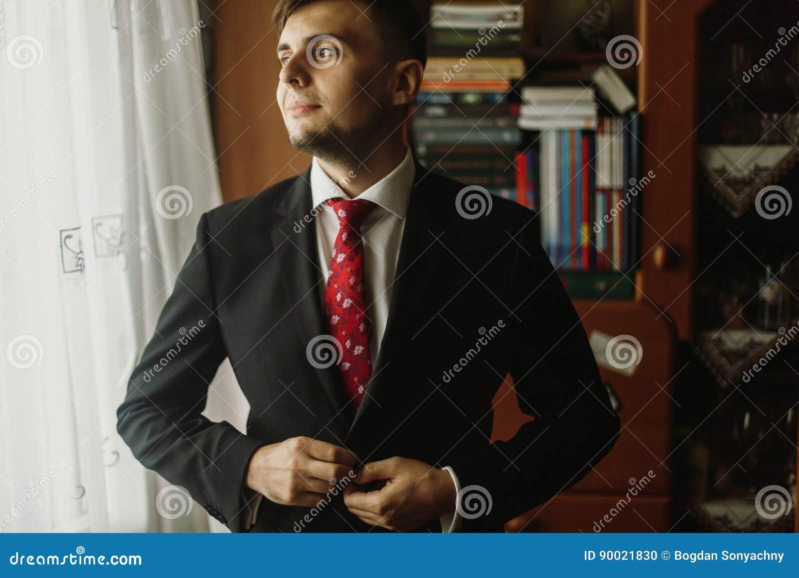 Noivo considerável na camisa branca com o laço vermelho que abotoa-se acima da SU preta