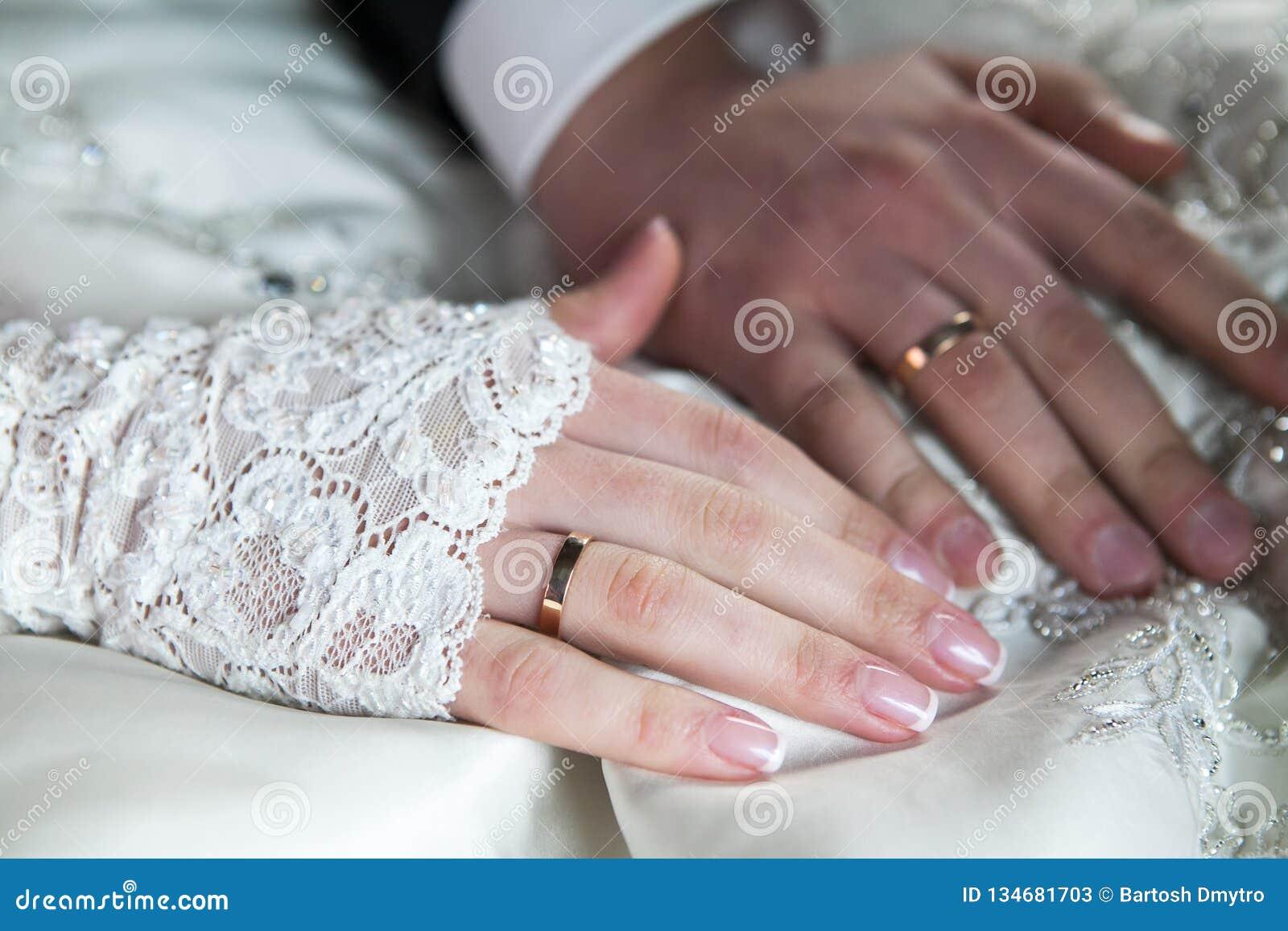 Noivo e noiva que guardam as mãos com alianças de casamento