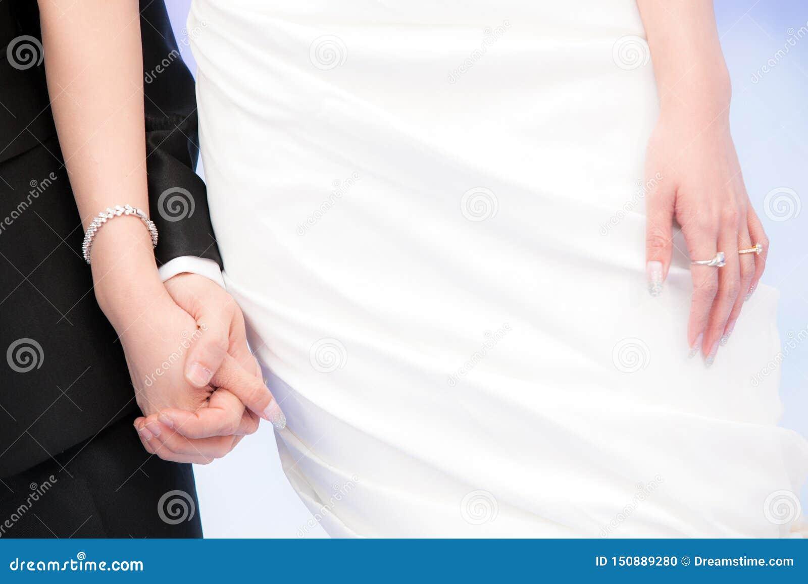 Noivo e noiva que guardam as mãos com anéis em seus dedos