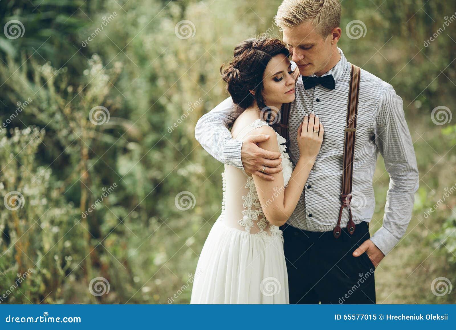 Noivo que abraça delicadamente sua noiva