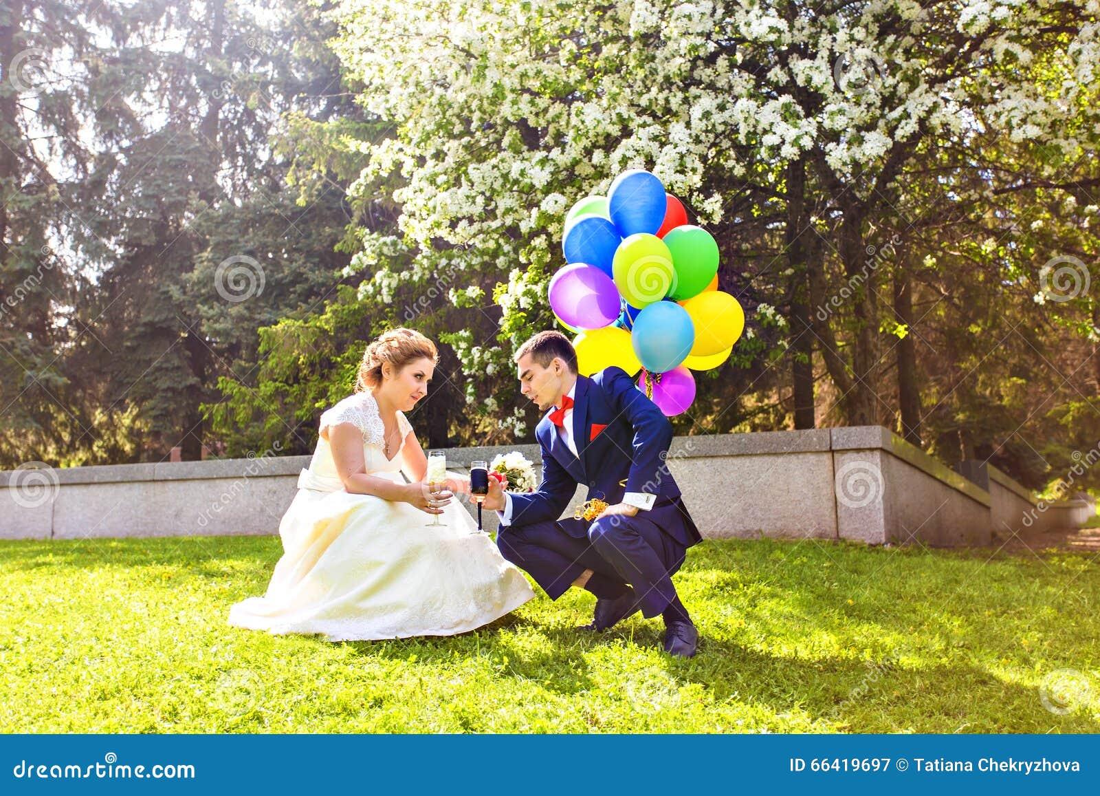 Noivos bonitos em um parque com balões coloridos