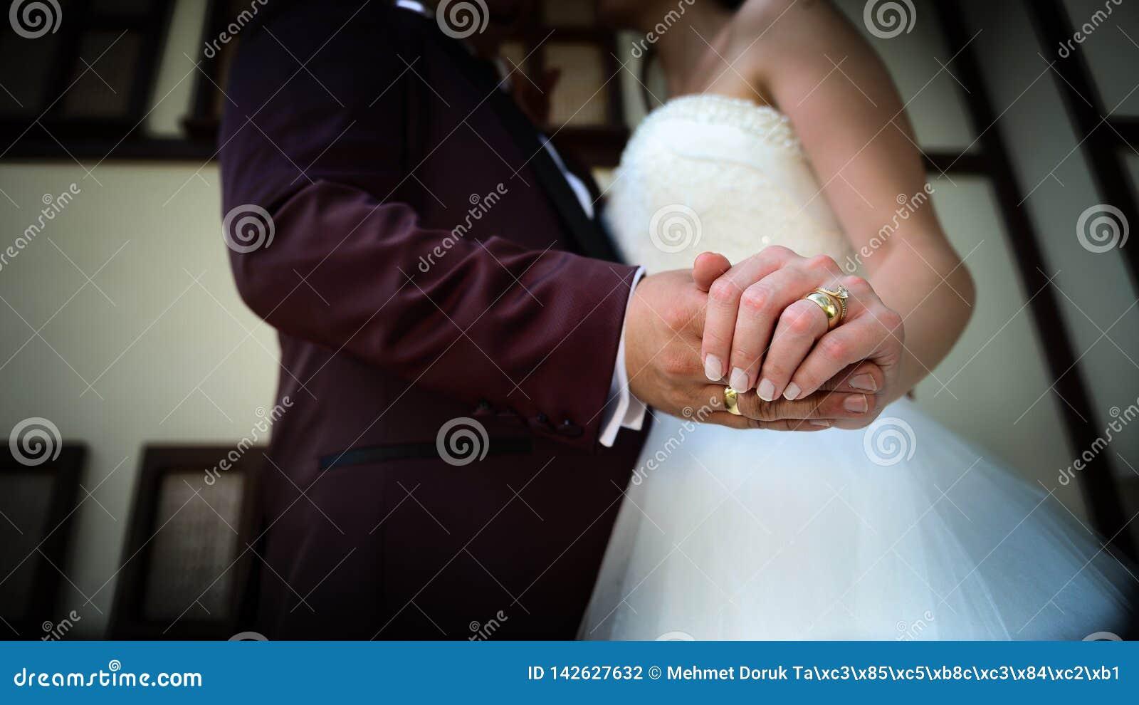 Noivos que guardam as mãos com aneis de noivado em seus dedos próximos acima do conceito do tiro do casamento da vista