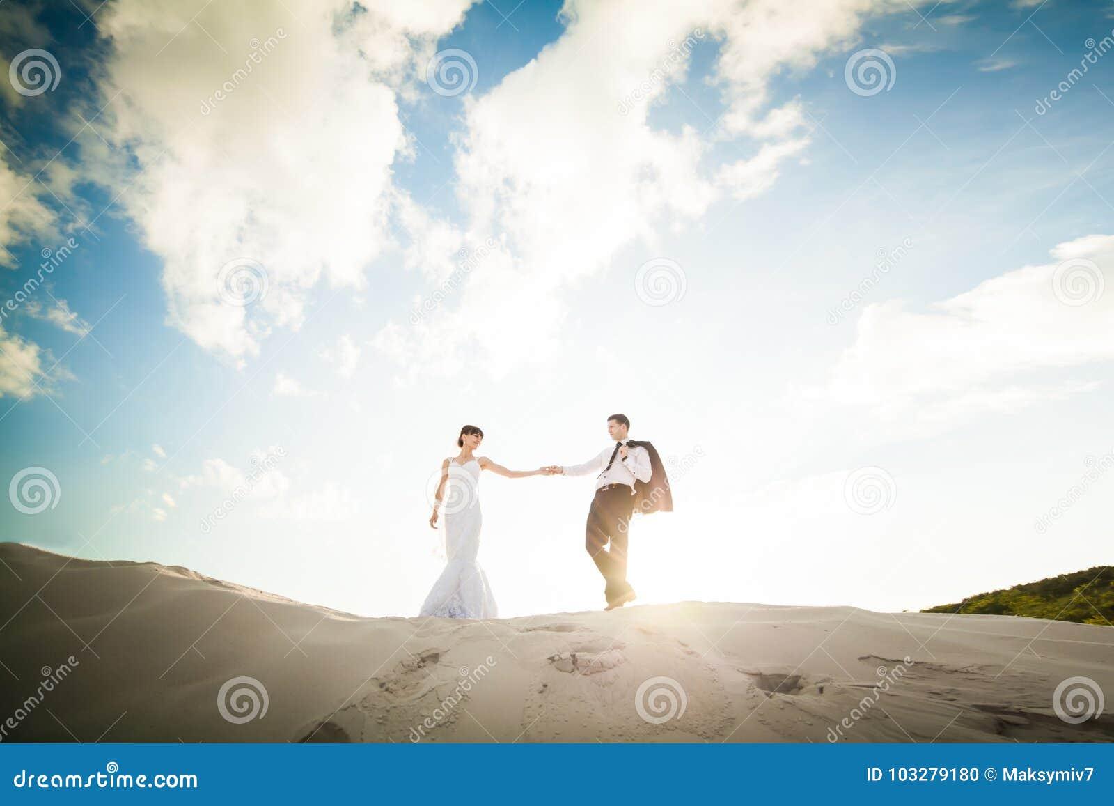 Noivos que guardam as mãos e o corredor através da areia no th
