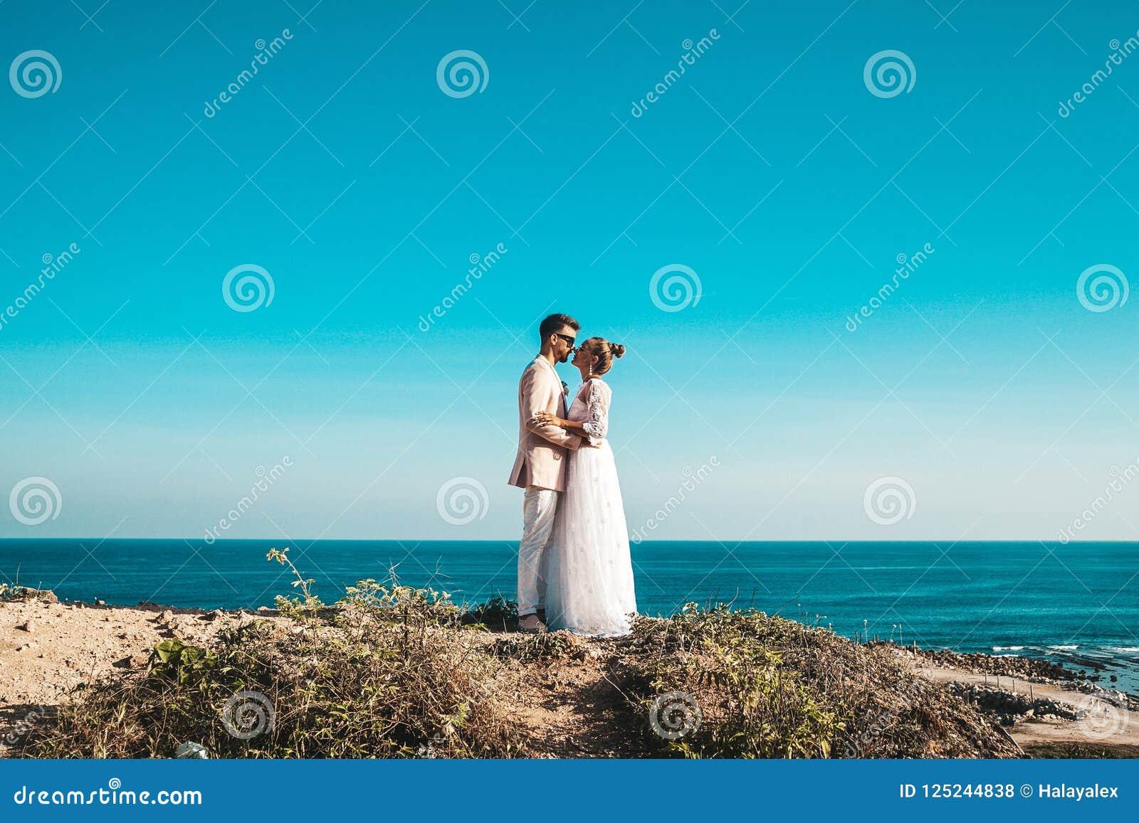 Noivos que levantam no penhasco atrás do céu azul e do mar Pares do casamento