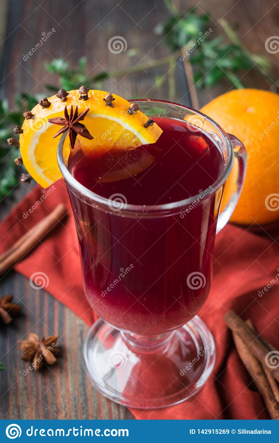Non-alcoholic mulled wine from grape juice with orange and spices in a glass goblet