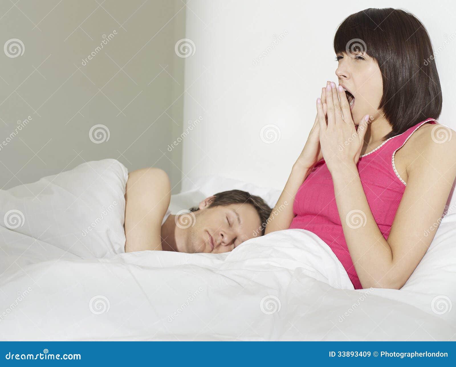 睡觉在妇女旁边的年轻人打呵欠在床上.