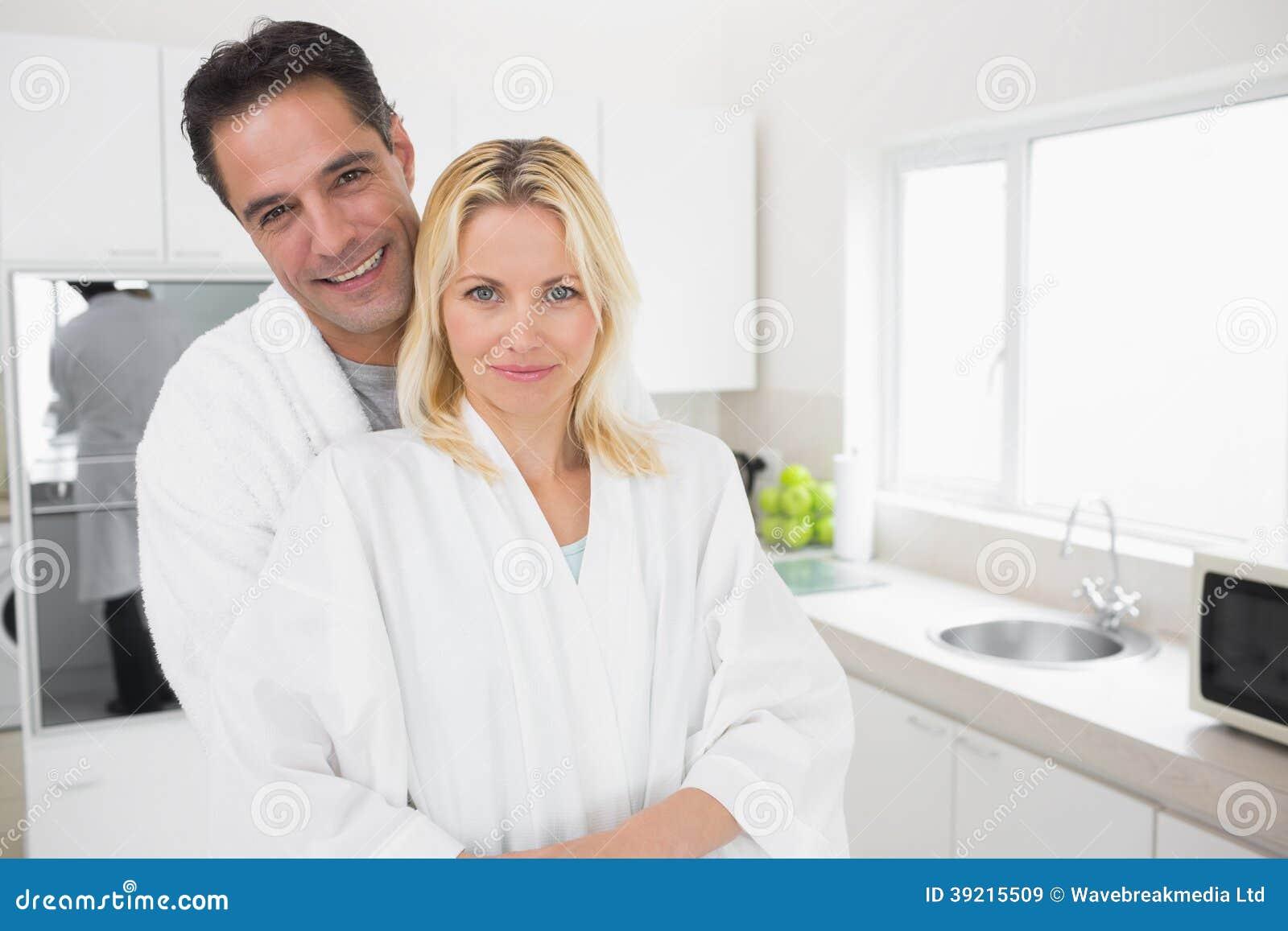 在家拥抱妇女从后面的画象人的在厨房里.图片