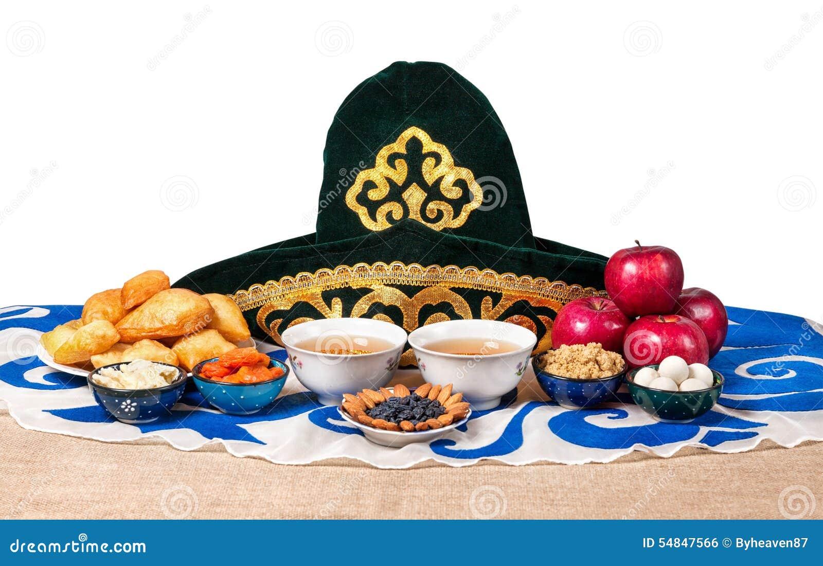 在桌上的哈萨克人全国在白色背景的食物与全国帽子和茶.
