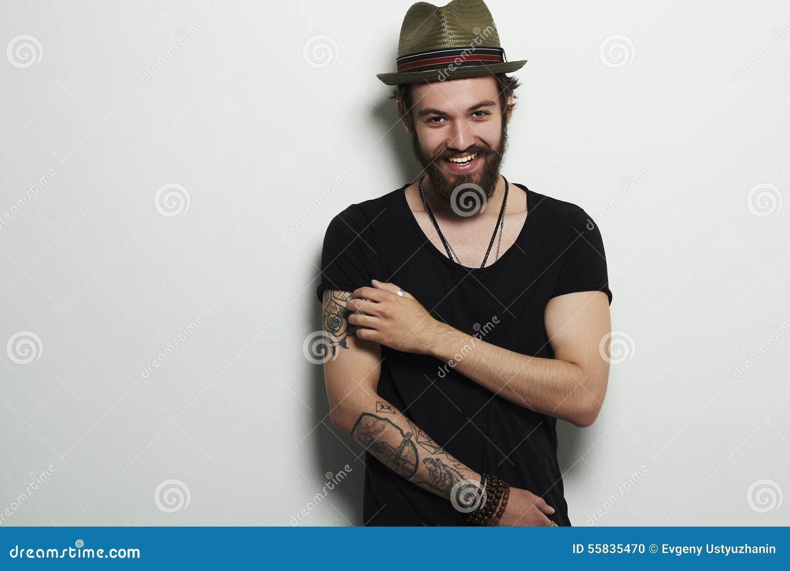 年轻有胡子的人时尚画象 微笑的行家男孩 帽子的英俊的人 有纹身花刺