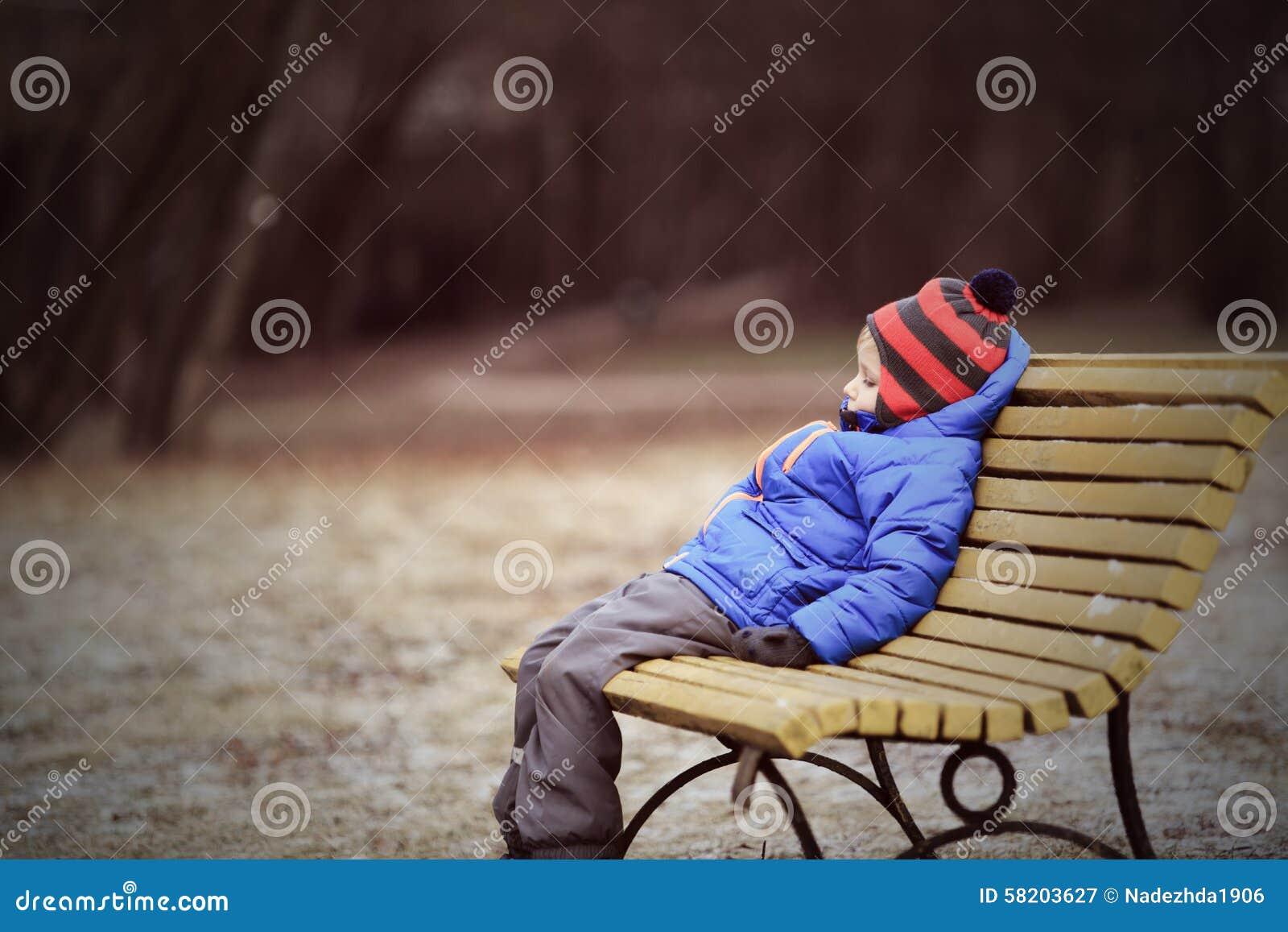 孤独的孩子坐长凳在公园,冬天消沉.