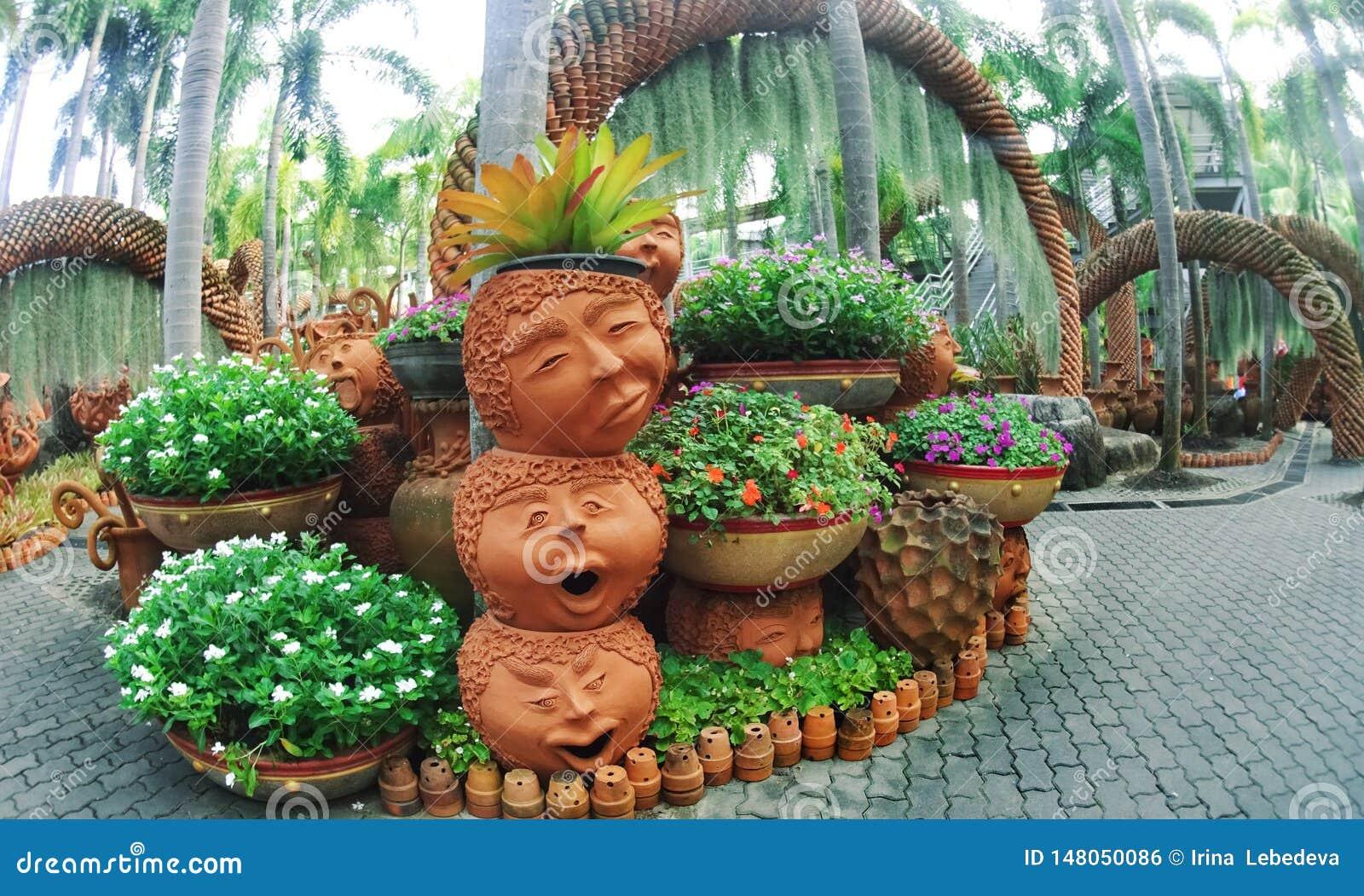 Nong Nooch park Pattaya z niezwykłym krajobrazowym projektem ceramiczni garnki w postaci śmiesznych twarzy i udziały greenery
