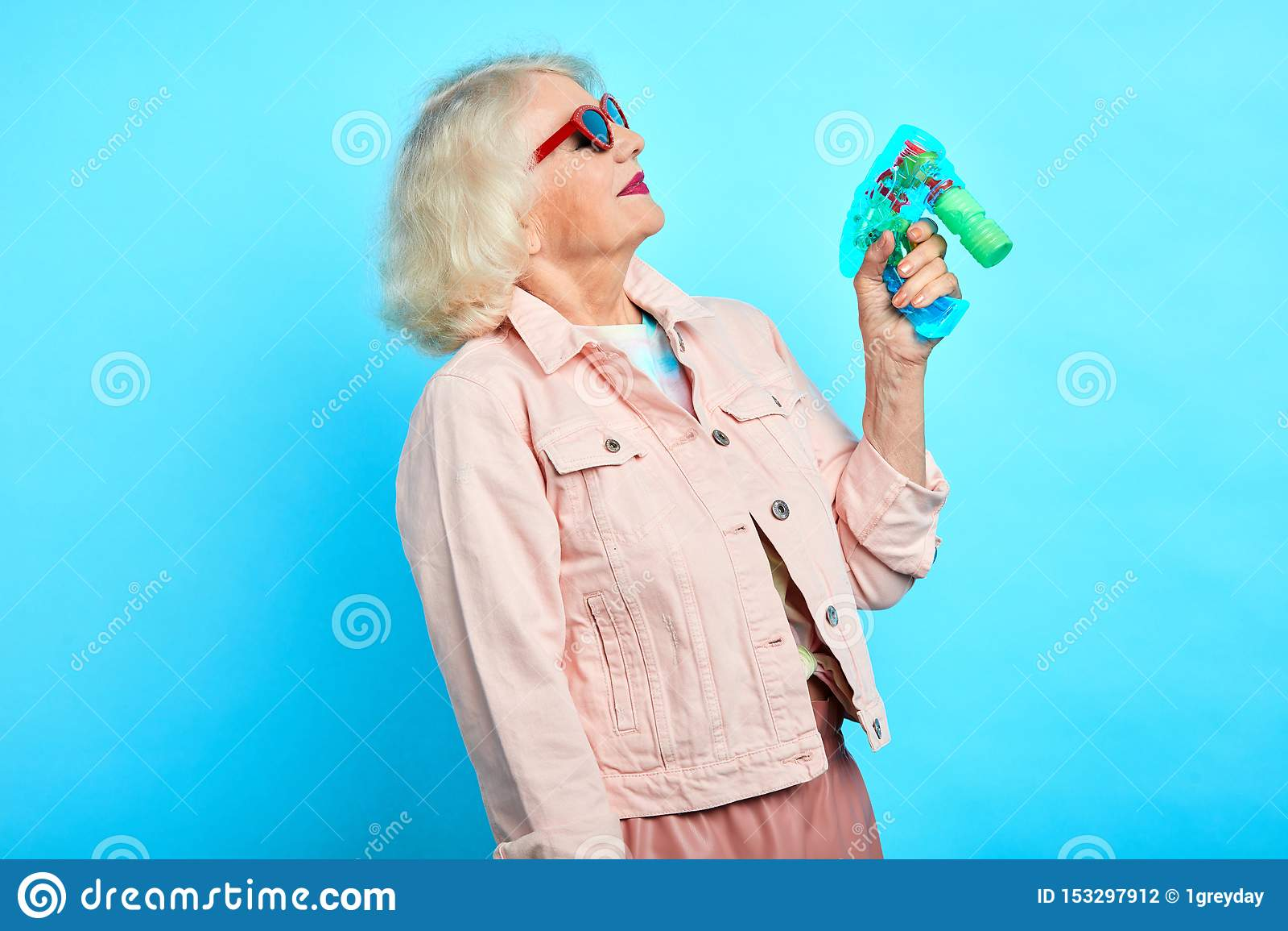 Nonna divertente pazza puerile che tiene una pistola del giocattolo, giocante con