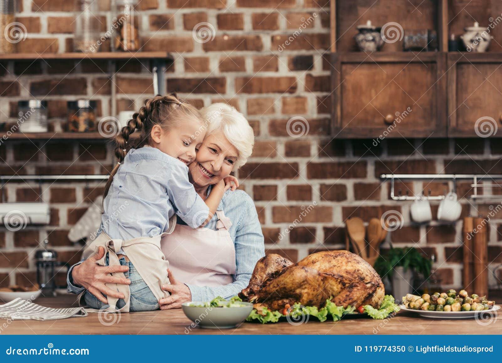 Nonna e nipote che abbracciano sulla cucina e che esaminano tacchino appena preparato