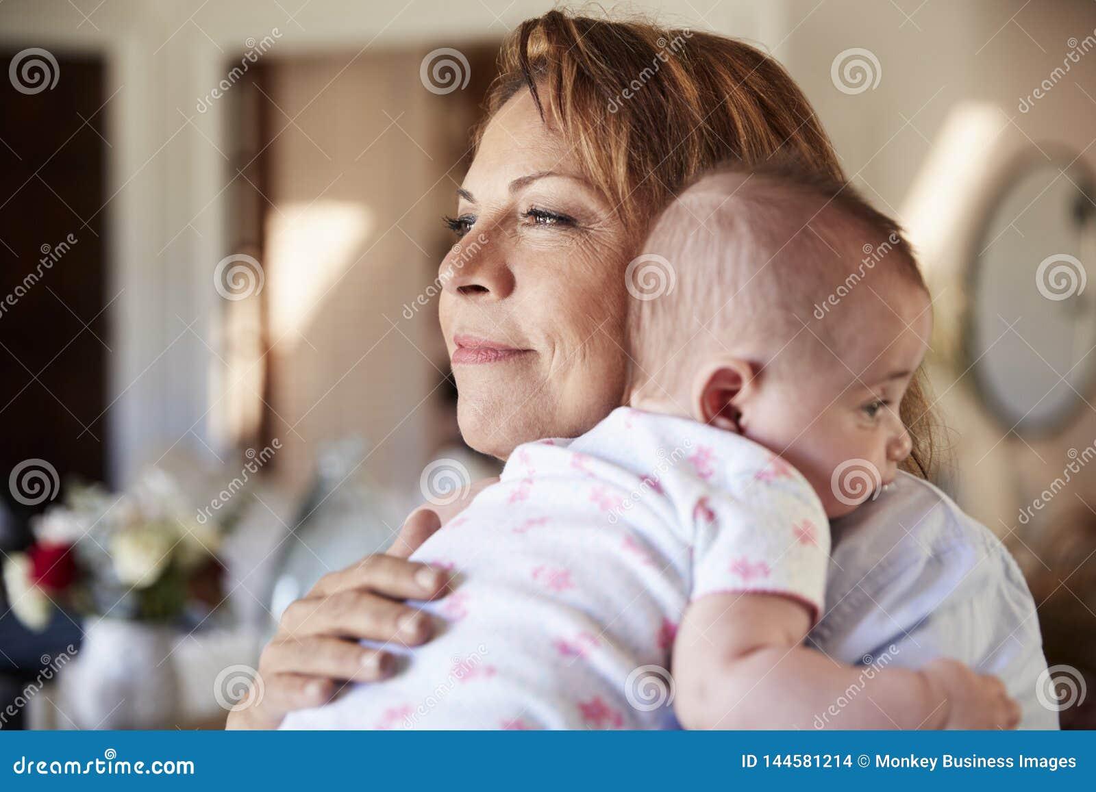 Nonna ispana invecchiata media che tiene il suo nipote neonato, di gran lunga, fine su