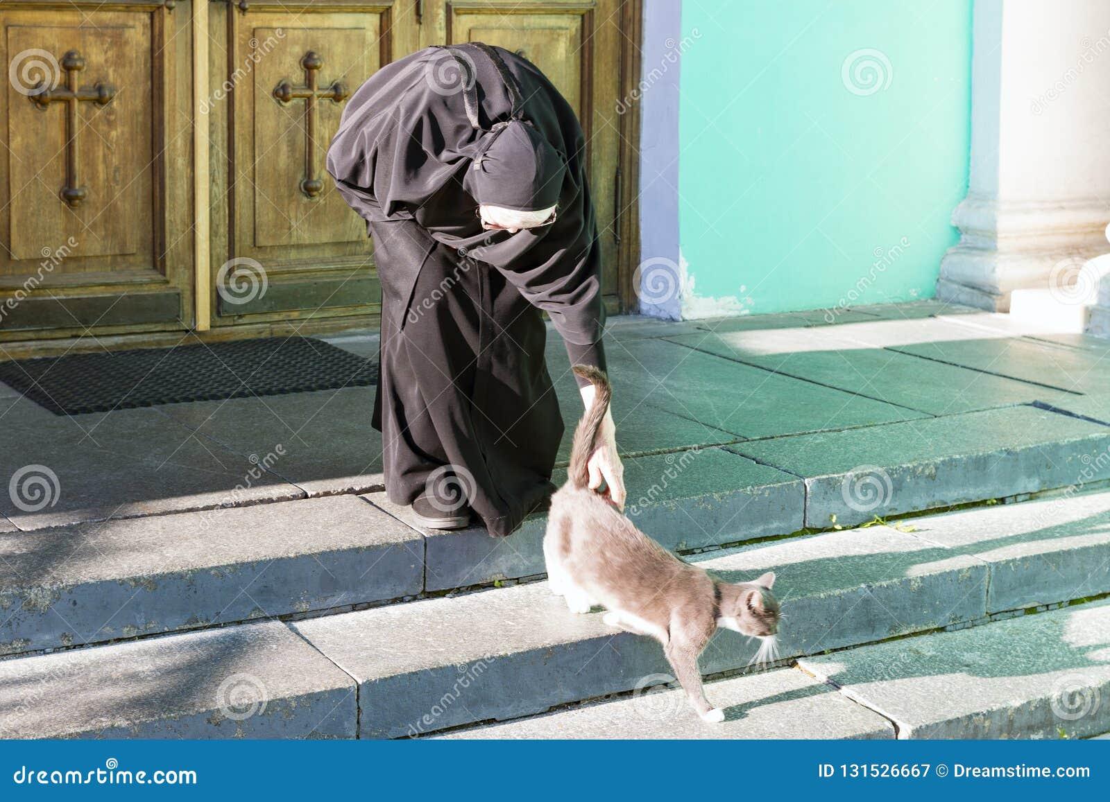 Nonne, die eine Katze streichelt