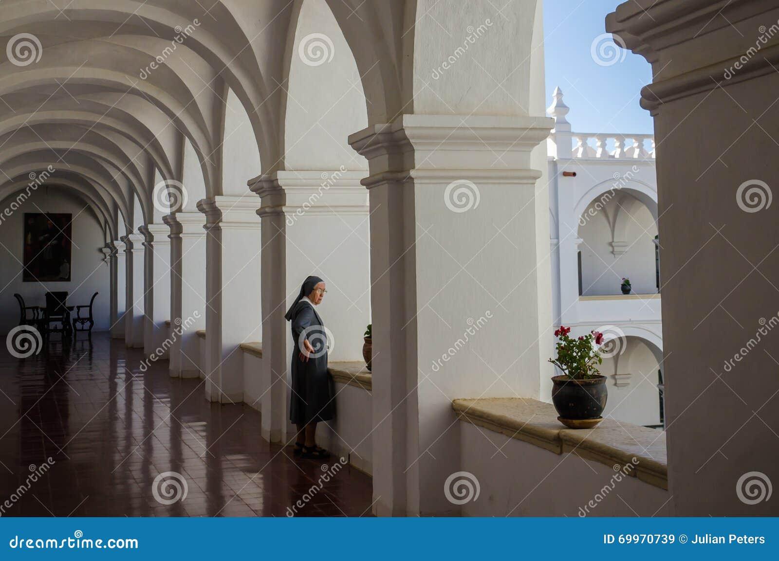 Nonne im Kloster schaut aus Fenster heraus
