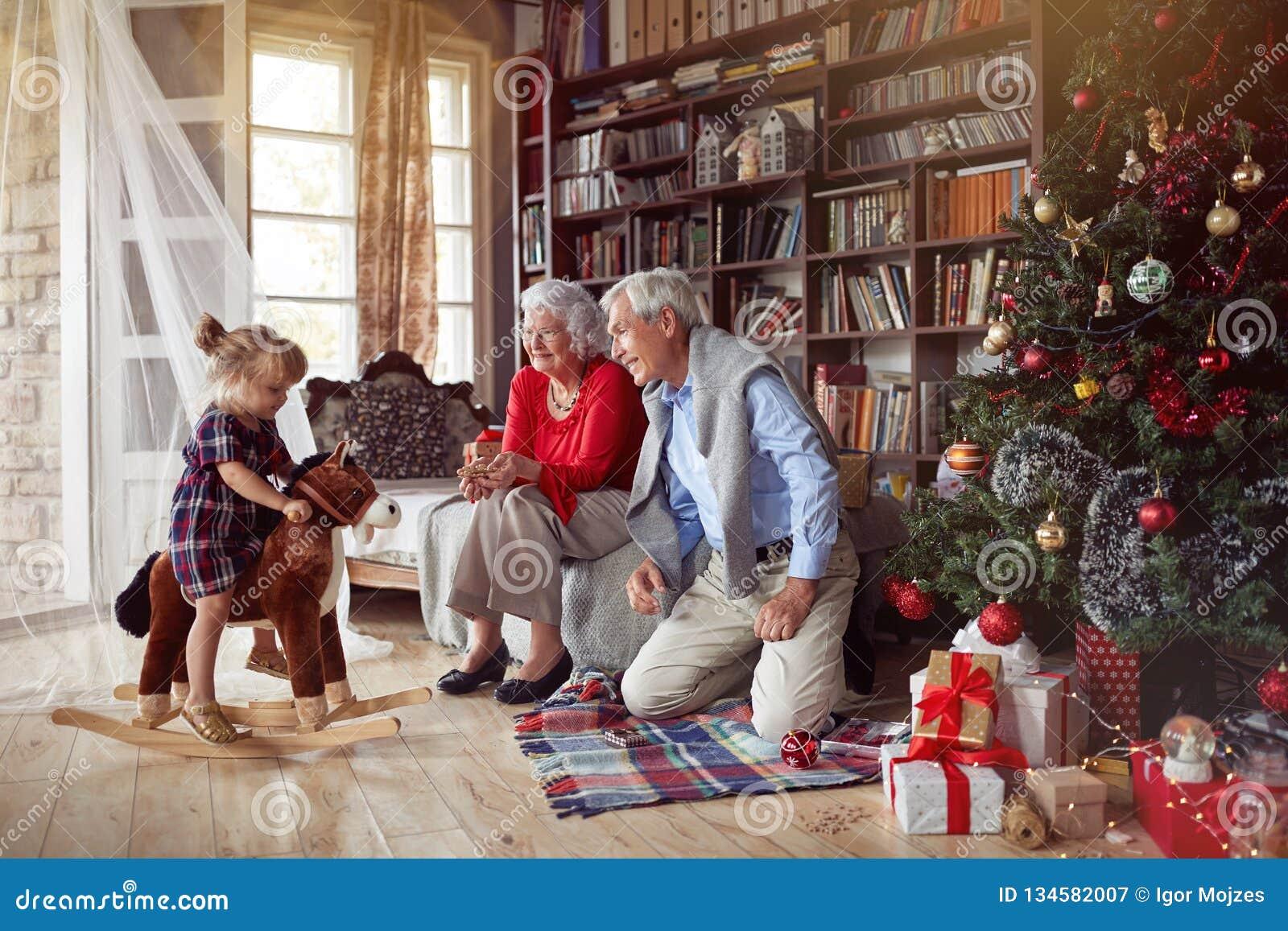 Nonni allegri e bambina che giocano insieme per il Natale