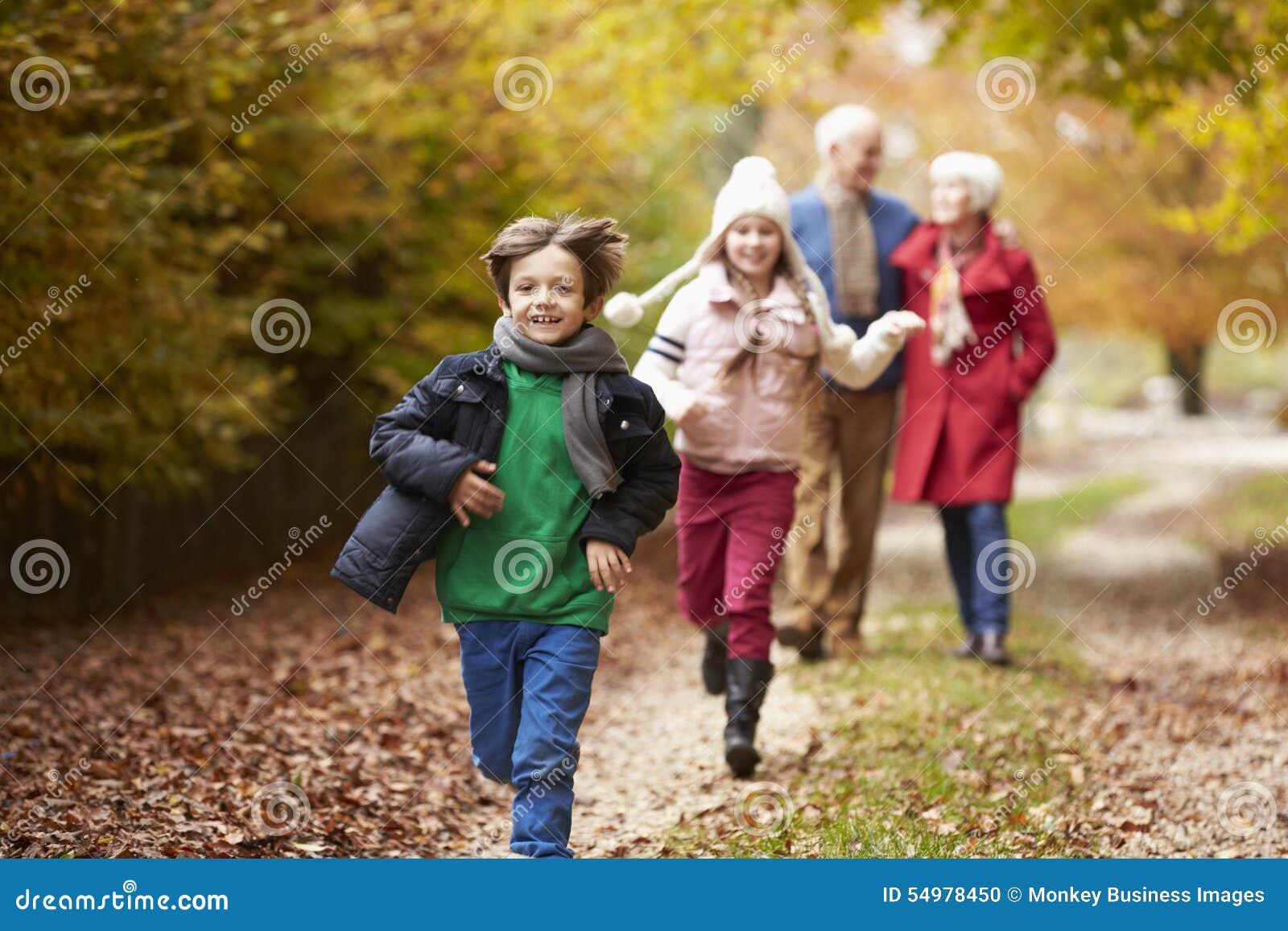 Nonni con i nipoti che corrono lungo Autumn Path