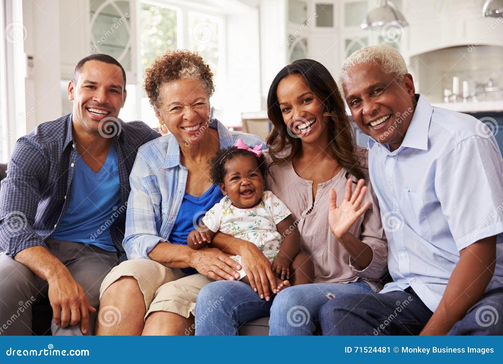 Nonni e genitori con una neonata sul ginocchio del ½ s del ¿ del mumï