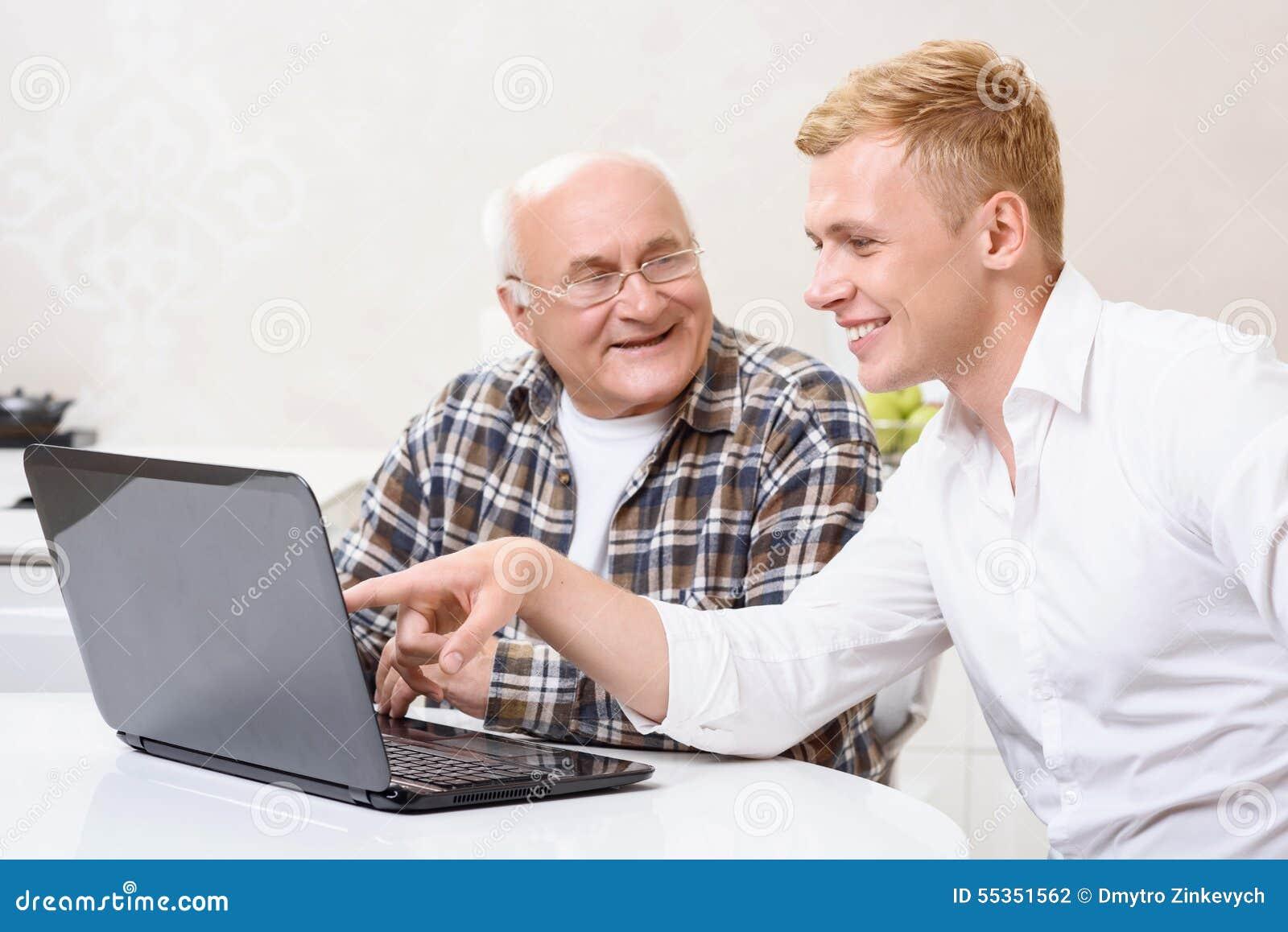 Nonno e nipote che si siedono con il computer portatile