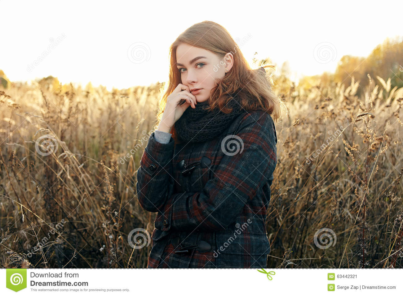 Noon portrait young beautiful redhead woman in scarf and plaid jacket on faded meadow cold season outdoors