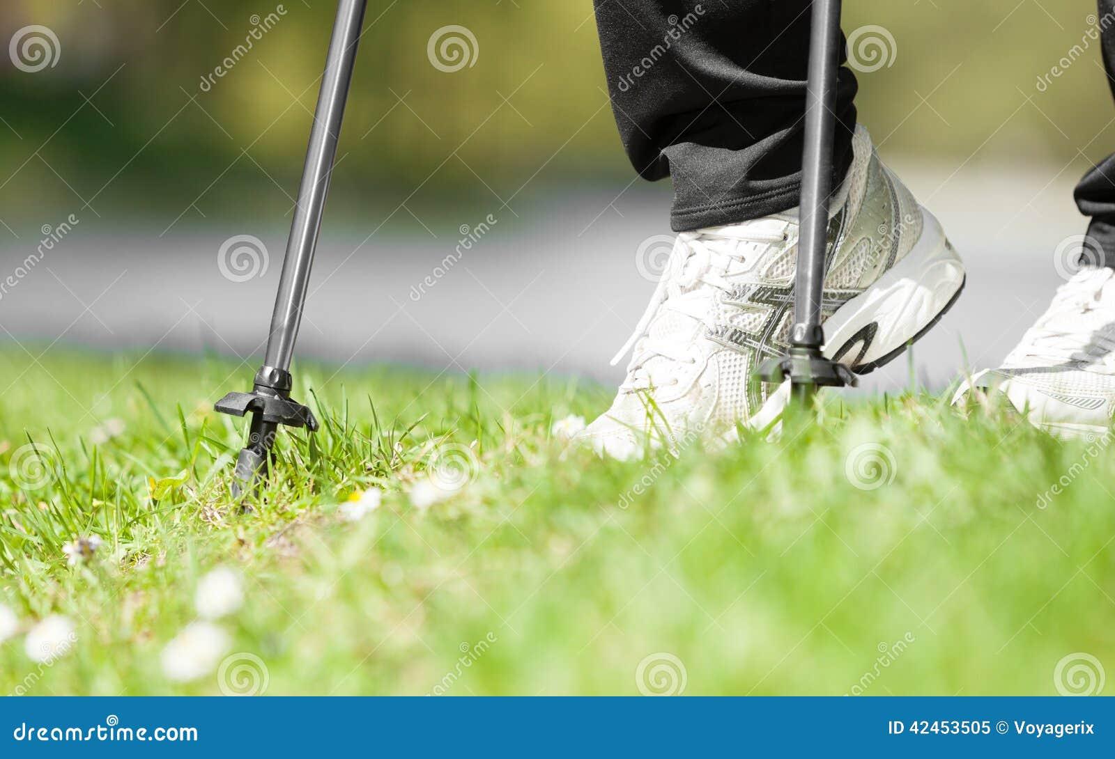 Nordisches Gehen Weibliche Beine, die im Park wandern