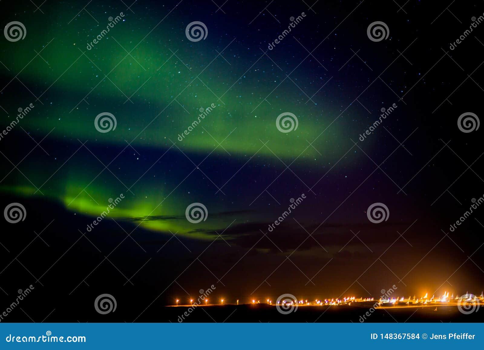 Nordlichter über einer Stadt in Island