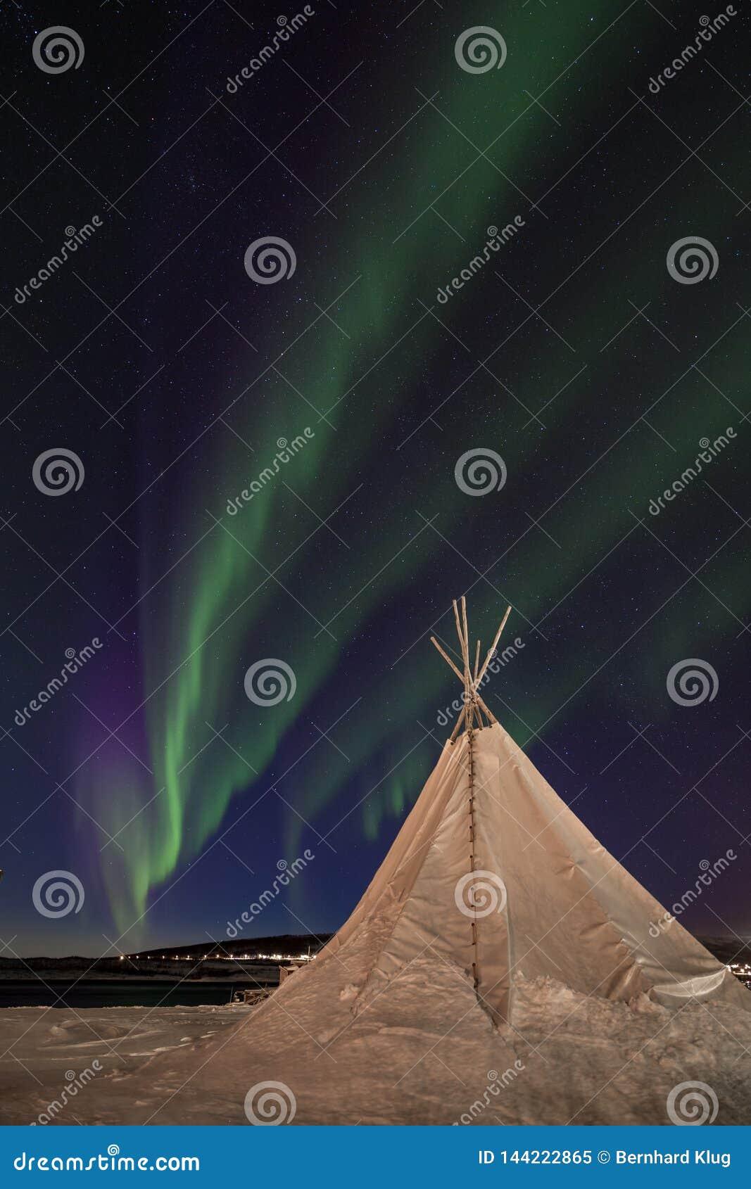 Nordlichter, die über ein traditionelles sami Zelt tanzen