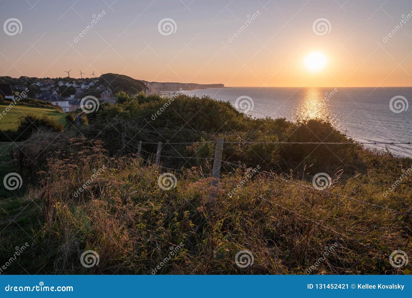 Normandie-Küstensonnenuntergangansicht von Klippen wässern und grasartiger Hügel in Frankreich