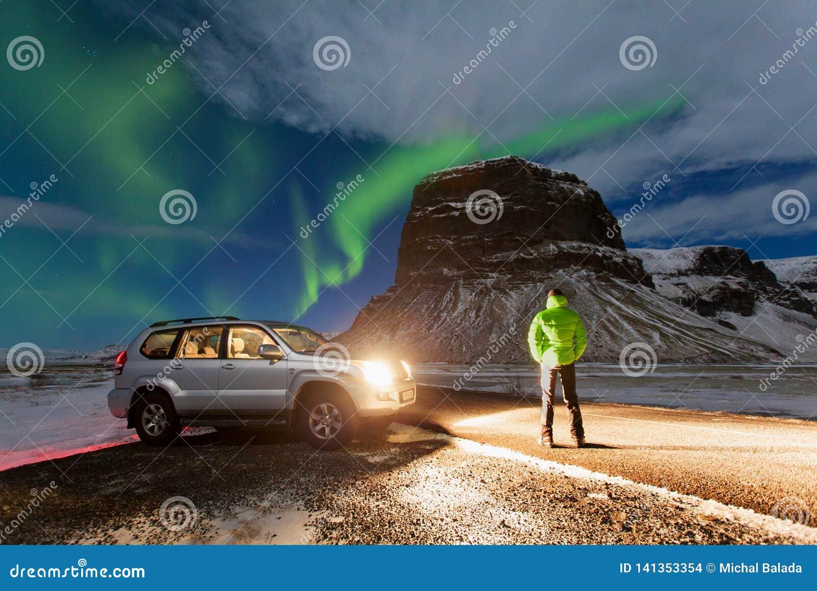 Norrsken ovanför mannen och bilen i Island nordliga klartecken Stjärnklar himmel med polara ljus