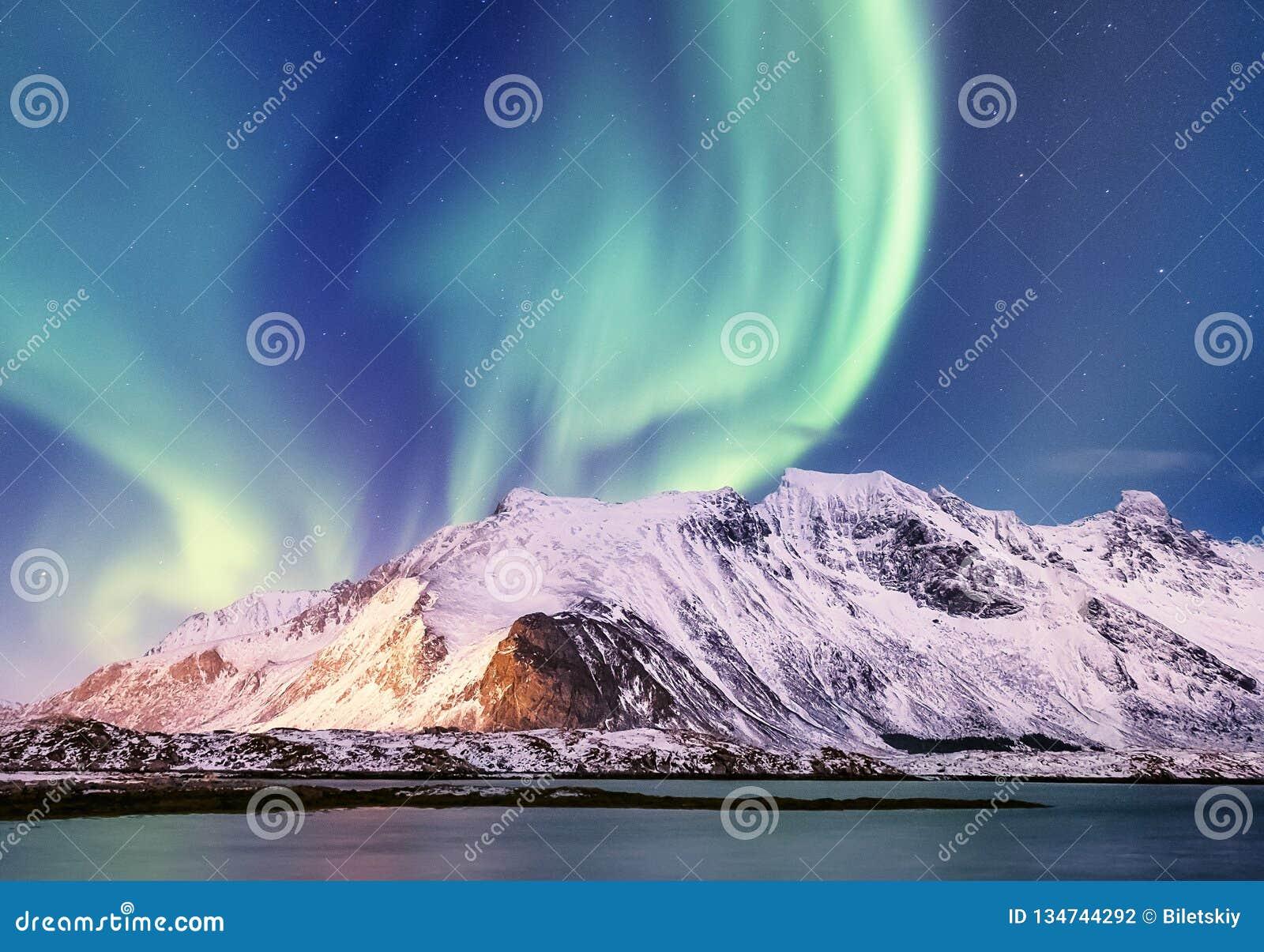 Norrsken på de Lofoten öarna, Norge Gröna nordliga ljus ovanför berg Natthimmel med polara ljus Nattvinter l