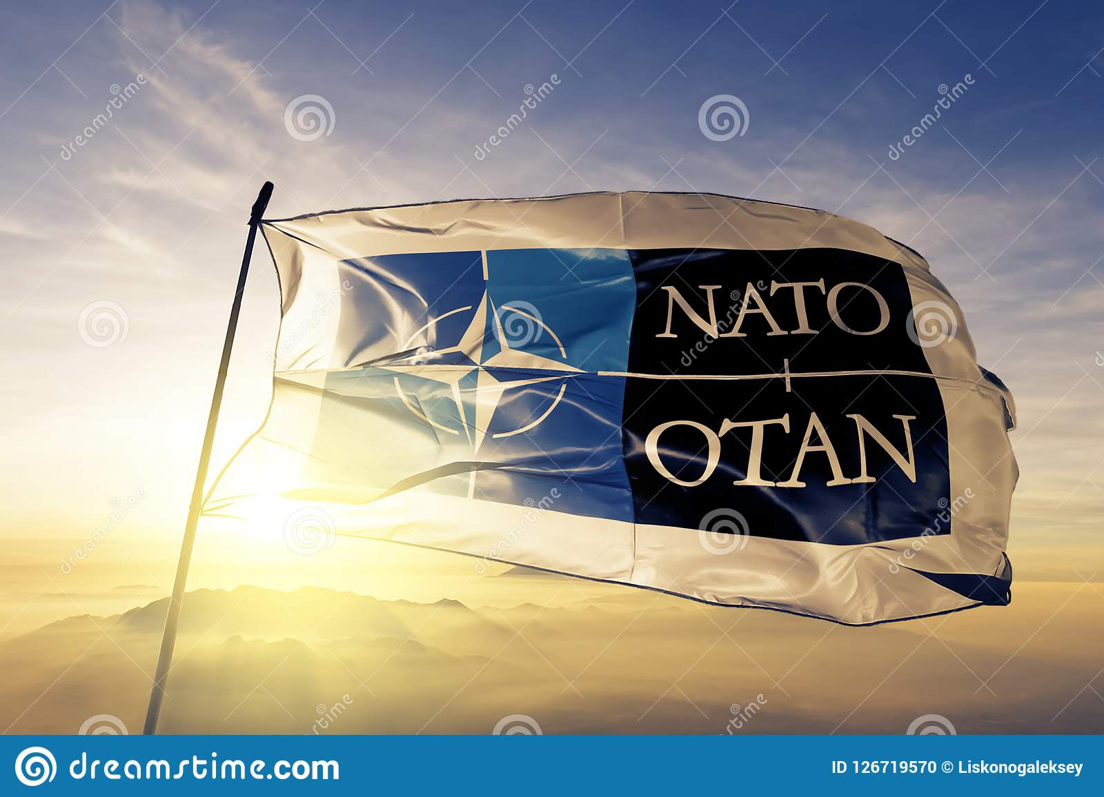 North Atlantic Treaty Organization NATO OTAN logo. flag textile cloth fabric waving on the top sunrise mist fog