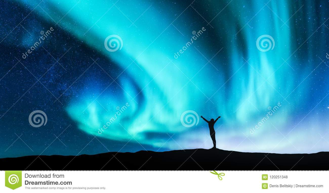 Northern lights and silhouette of a woman with raised up arms