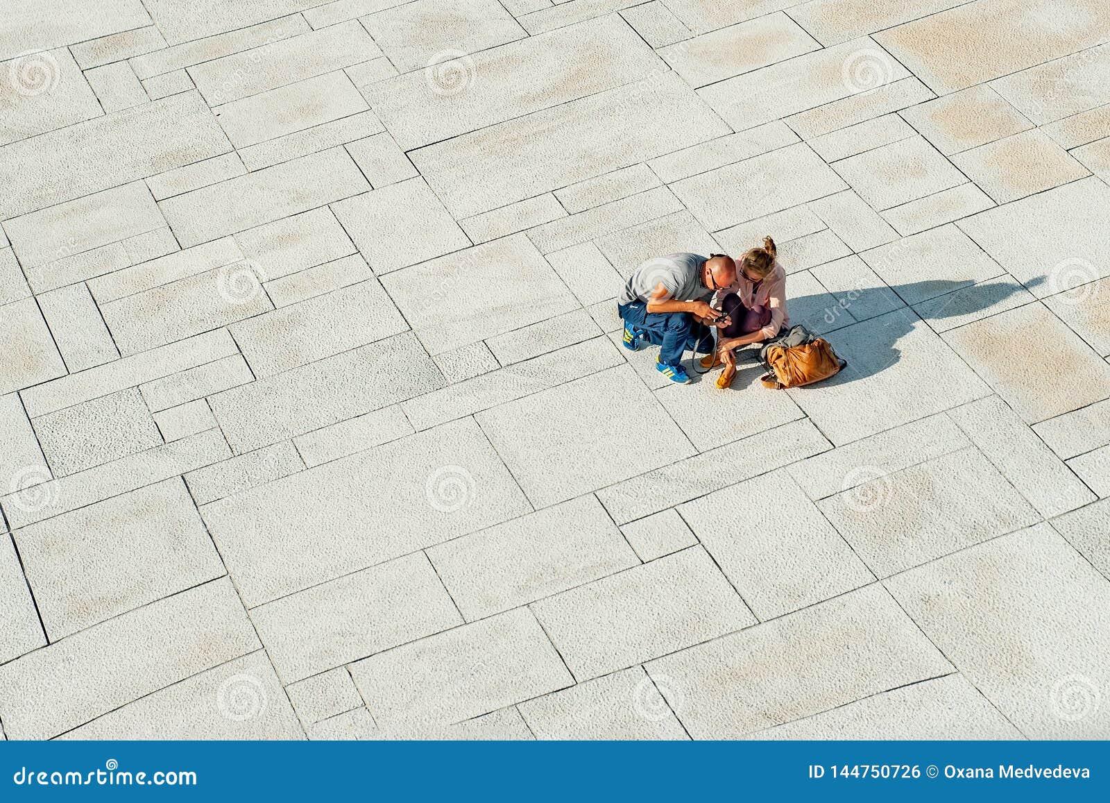Noruega, Oslo 1? de agosto de 2013: Dois turistas dos jovens para relaxar e ver fotos na margem do teatro da ?pera em Oslo em
